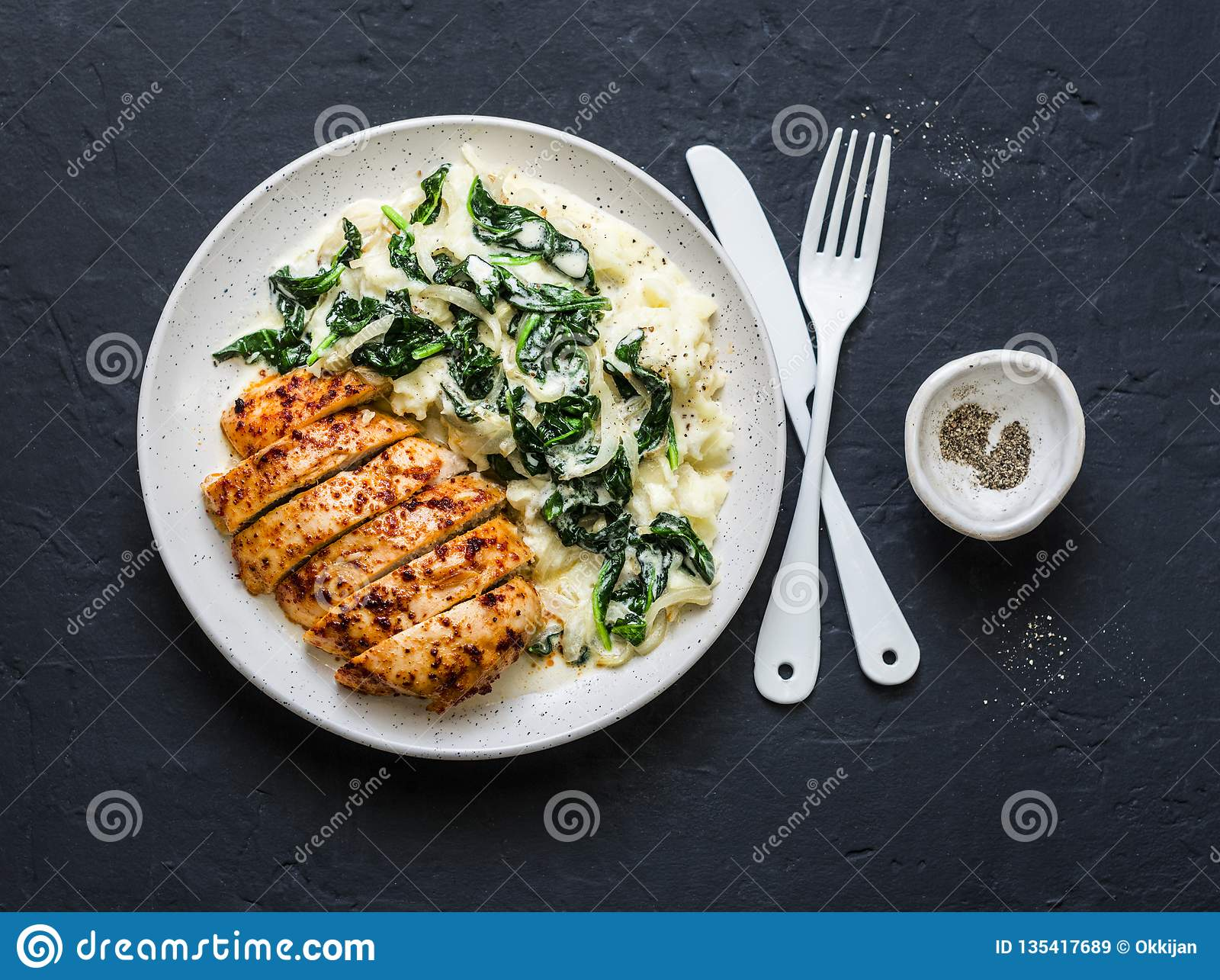 Baked chicken breast, mashed potatoes with creamy spinach on dark background, top view.