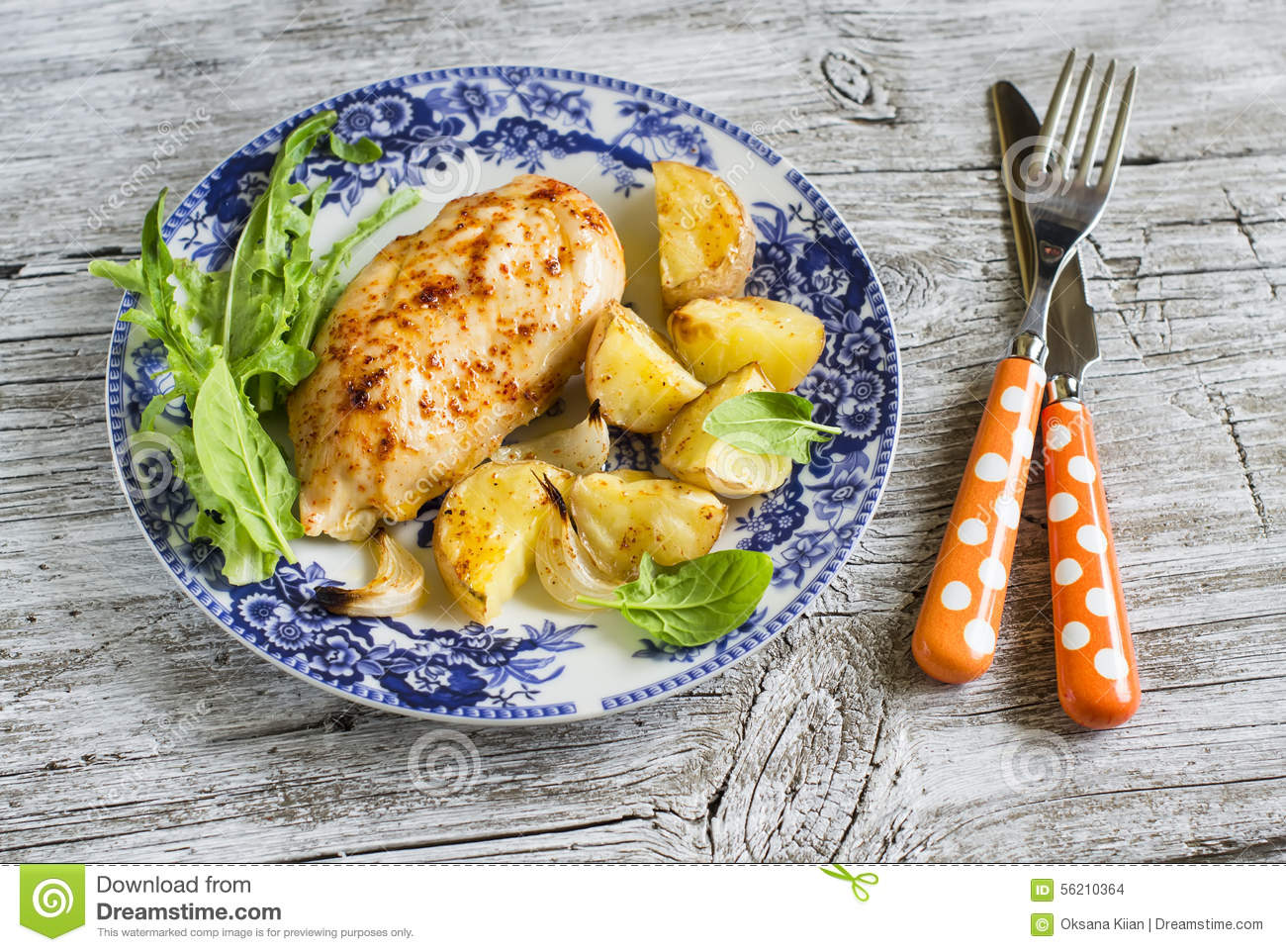 Baked chicken breast with potatoes and onions on a vintage plate