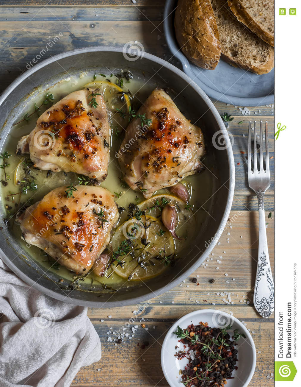 Baked chicken in white wine in the pan. On rustic wooden background