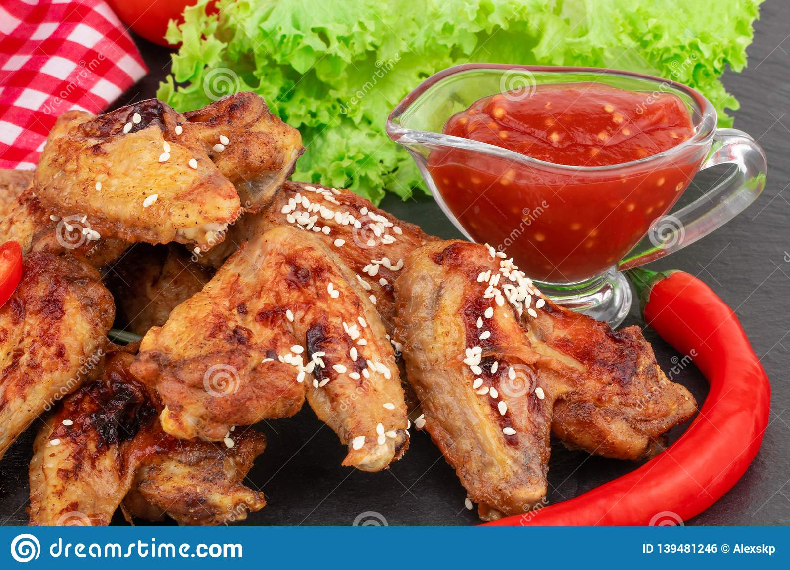 Baked chicken wings with sesame seeds and sweet chili sauce on dark background