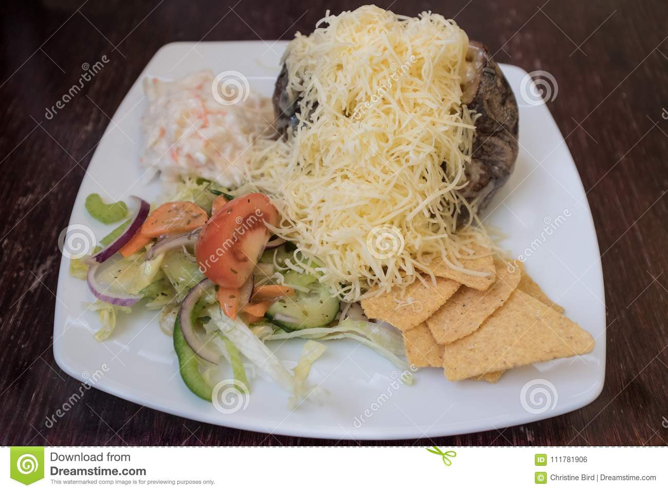 Baked potato with grated cheese, coleslaw and salad