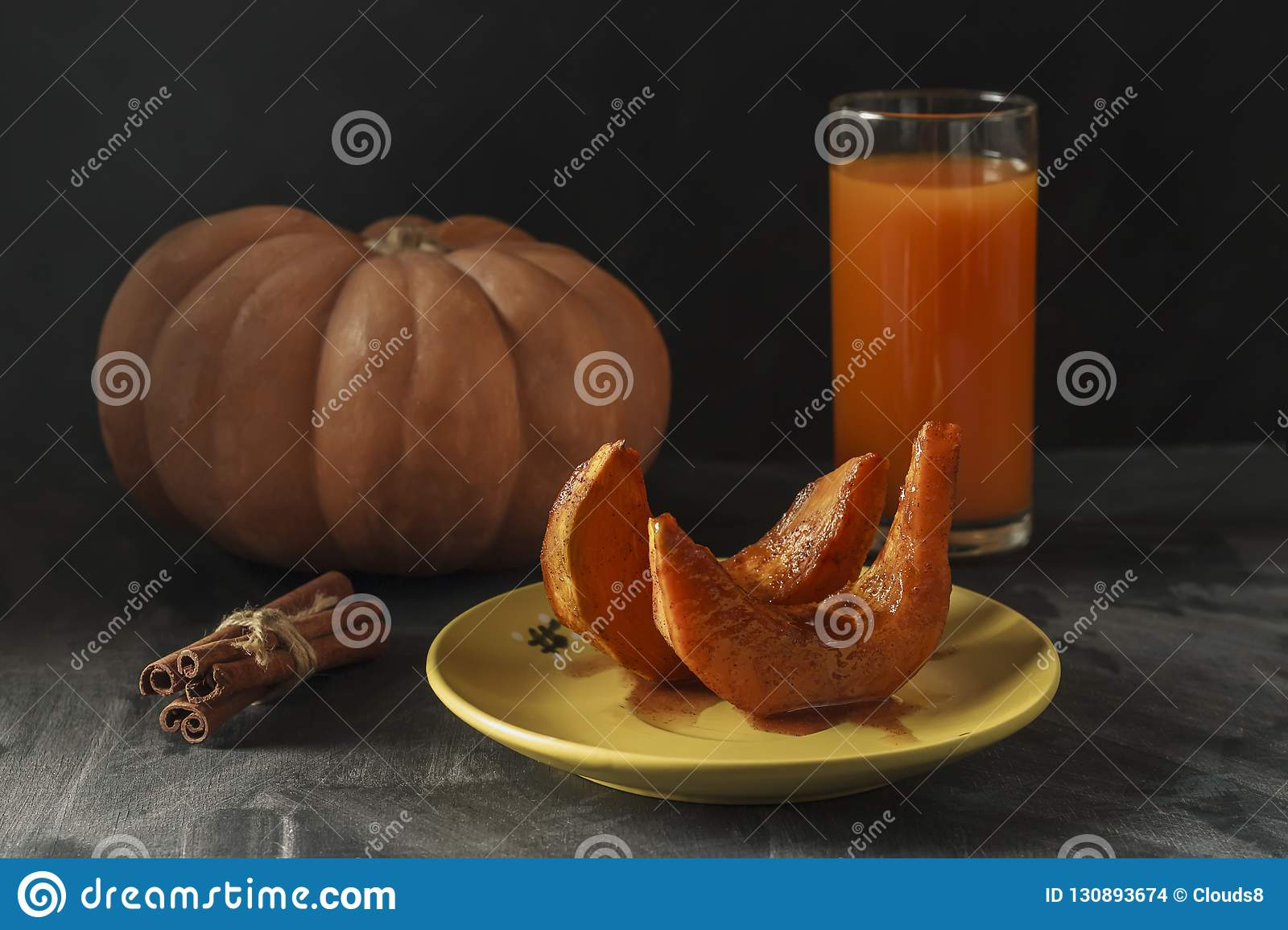 Baked pumpkin with cinnamon sticks, rustic spoon and a glass of juice