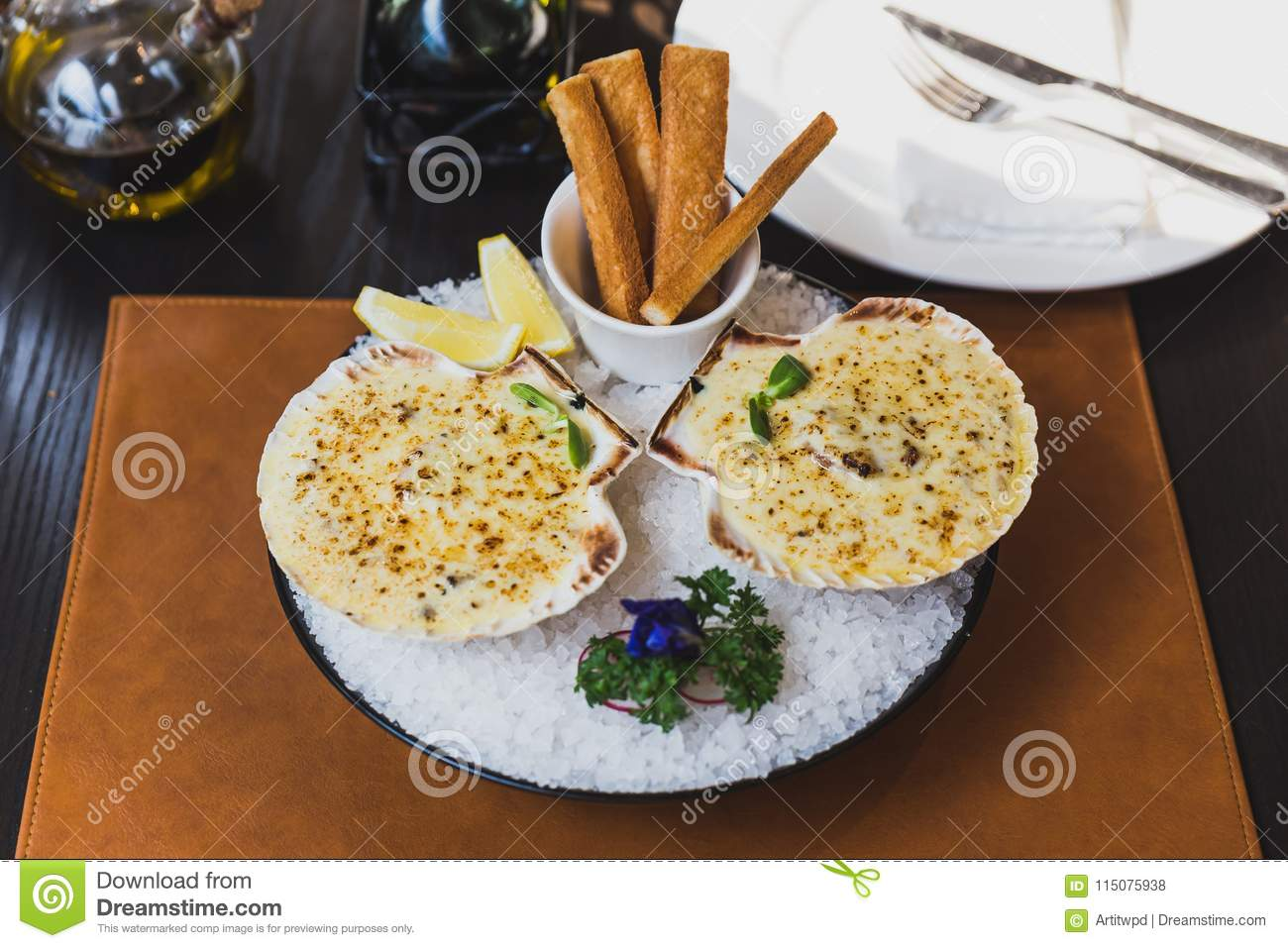 Baked scallops with cheese served with sliced lemon and bread sticks on bowl with full of sea salt