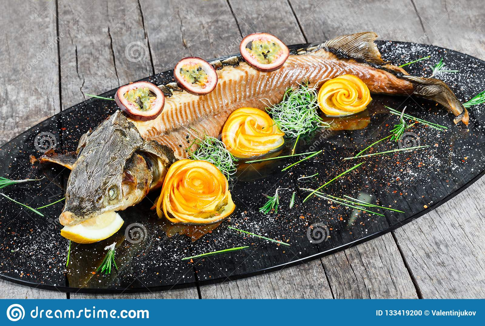 Baked sturgeon fish with rosemary, lemon and passion fruit on plate on wooden background close up.