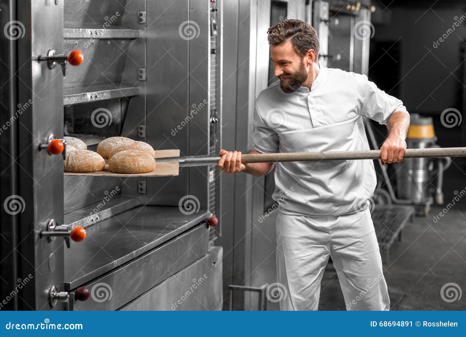 Baker που παίρνει έξω από το ψημένο φούρνος buckweat ψωμί