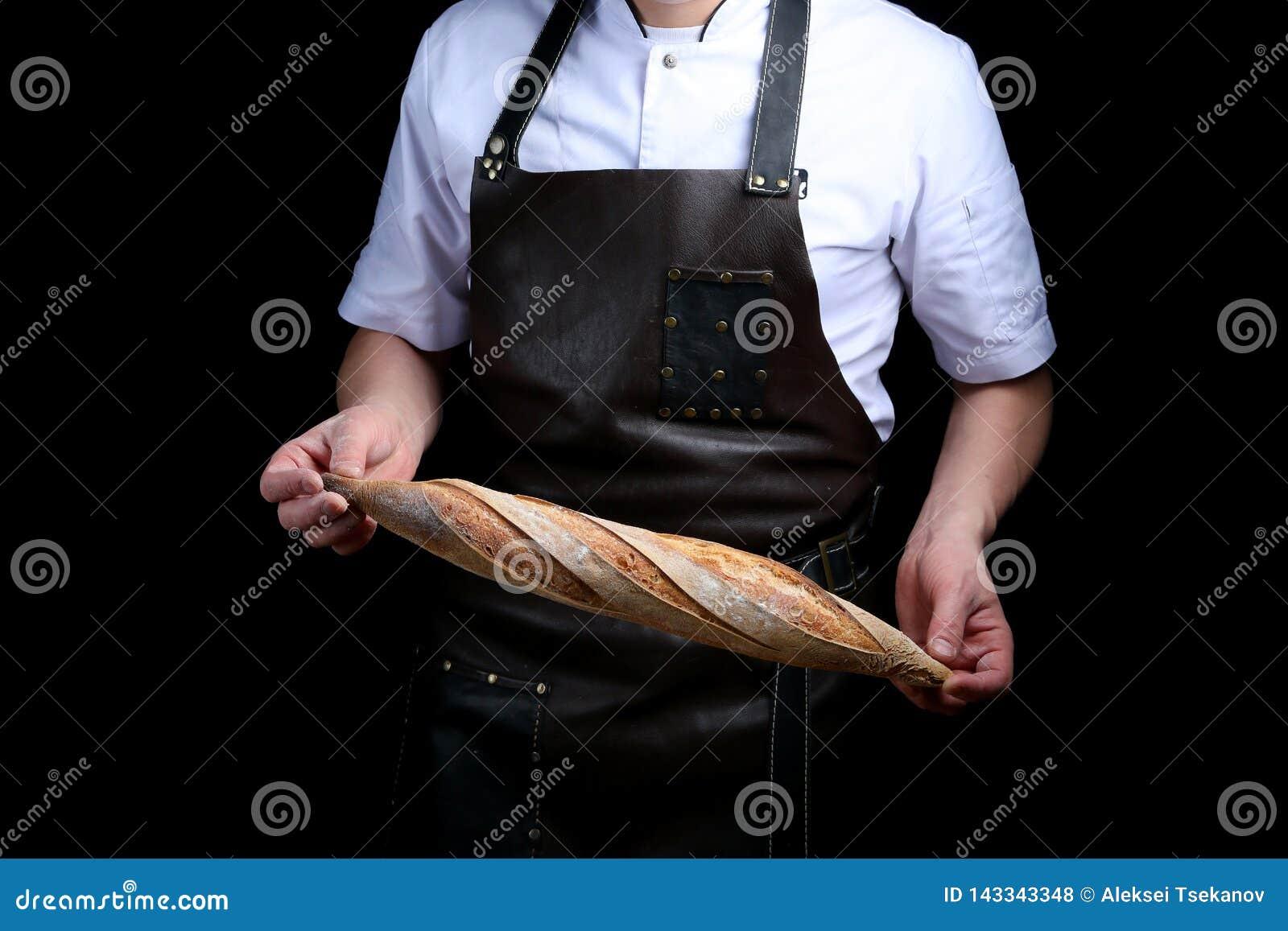 Baker houdt baguette op zwarte achtergrond wordt geïsoleerd die
