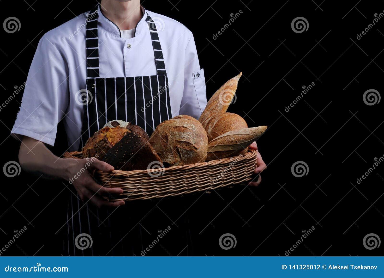 Baker houdt mand brood op zwarte achtergrond wordt geïsoleerd die