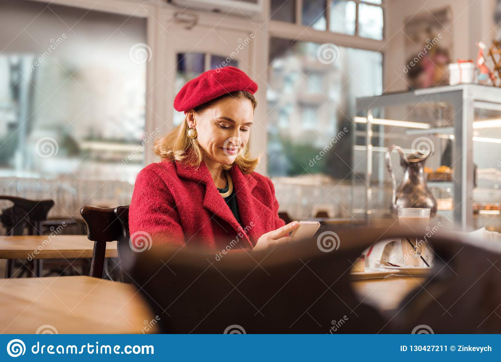 Mature appealing stylish woman feeling relaxed sitting in bakery on weekend