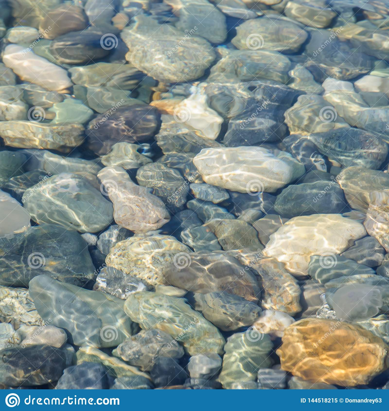 Bakgrund av havet färgade stenar under vatten