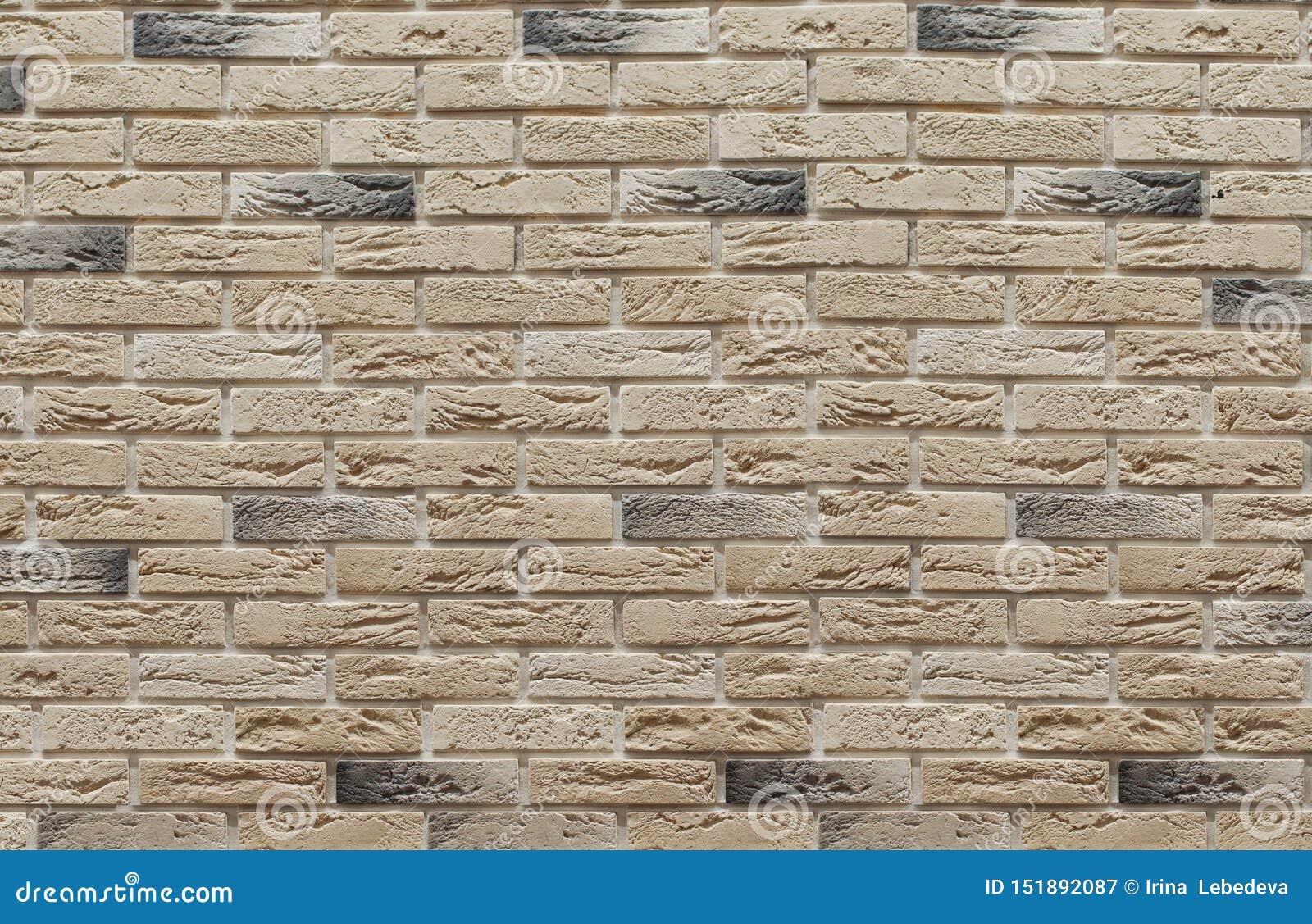 Bakgrund av murverkbrunt och beigea clinkertegelstenar på väggen, som används i reparationen av lokal