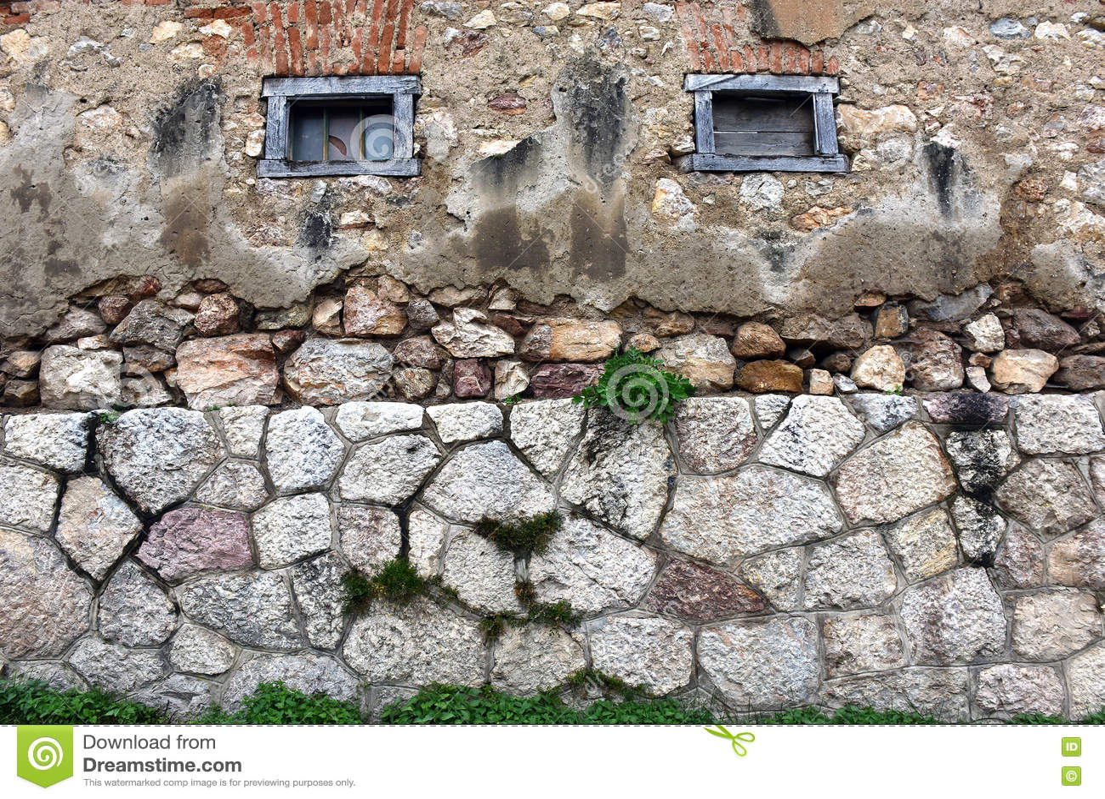 Bakgrund av stenväggen med små träfönster