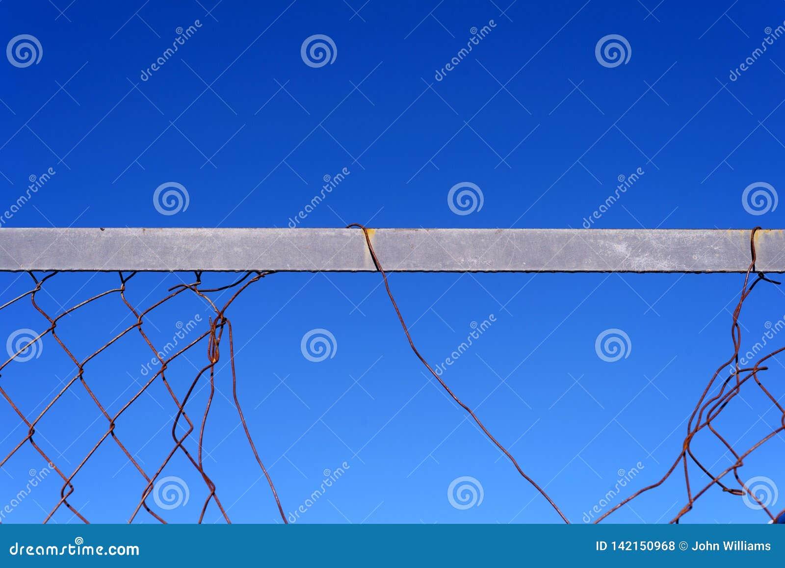 Bakgrund för brutet metalltrådstaket och för blå himmel