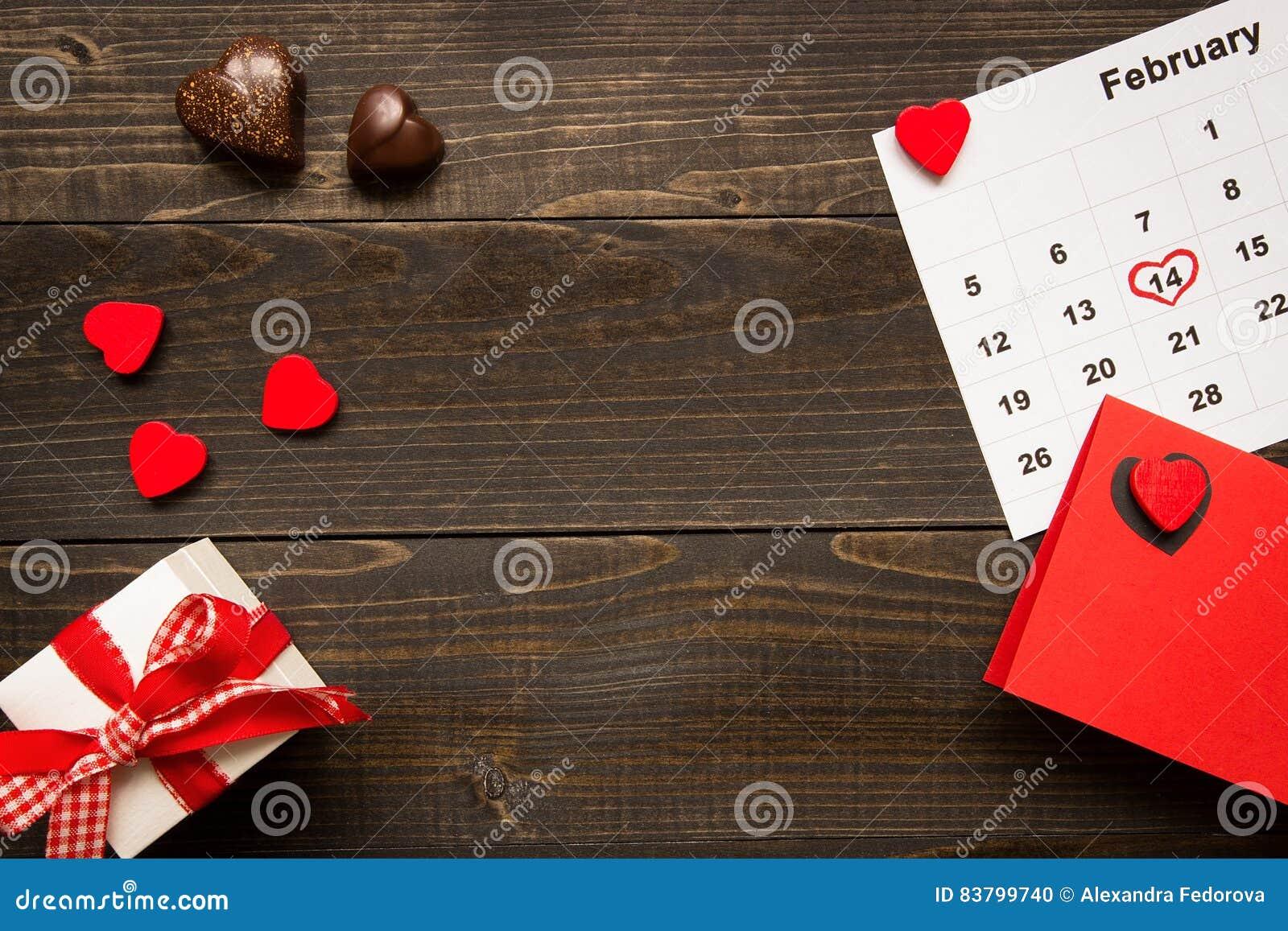 Bakgrund för dag för valentin` s med kopieringsutrymme Kort för dag för valentin` s, gåvaask och choklad på trätabellen