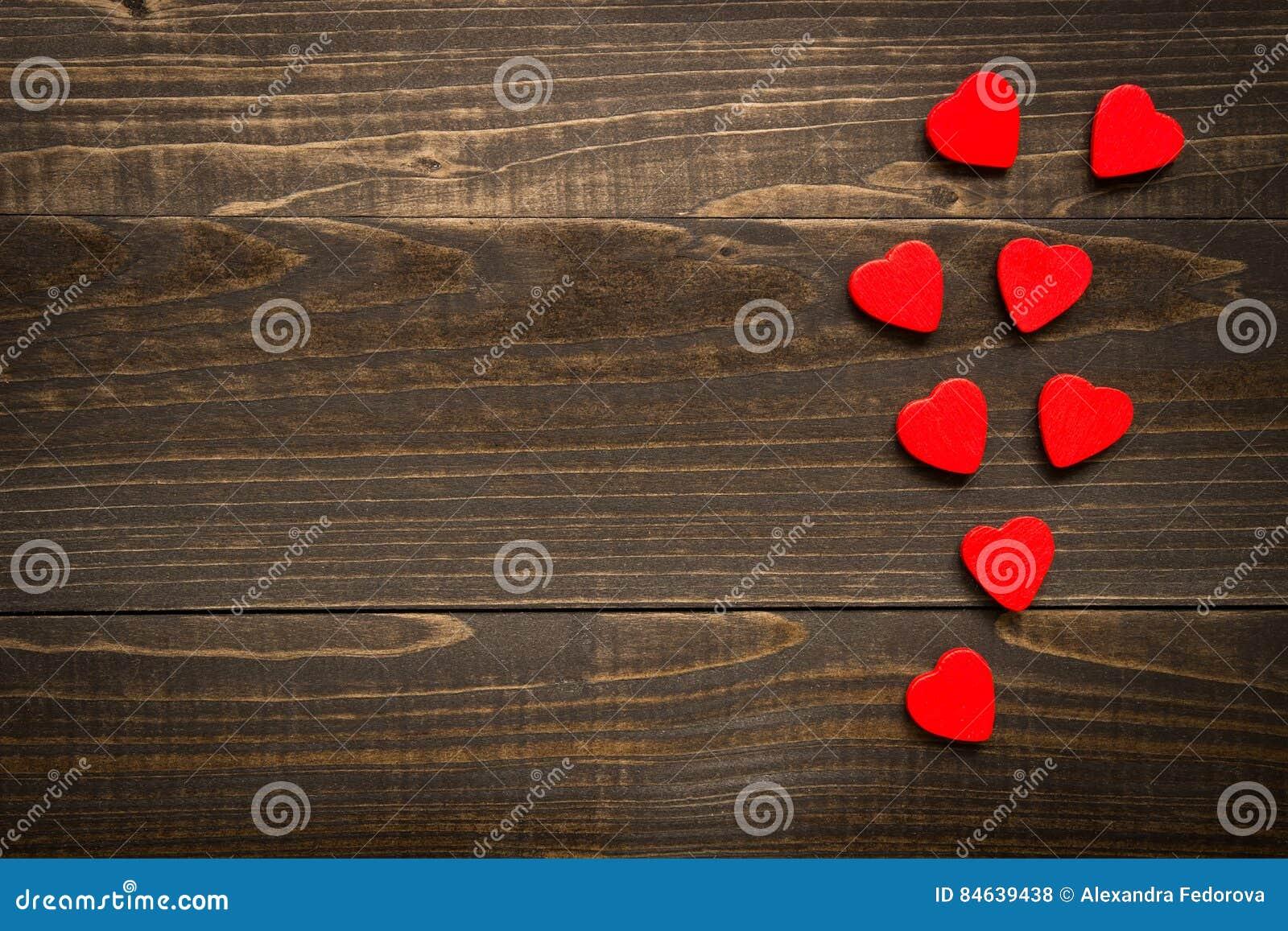 Bakgrund för dag för valentin` s Röda hjärtor på träskrivbordet