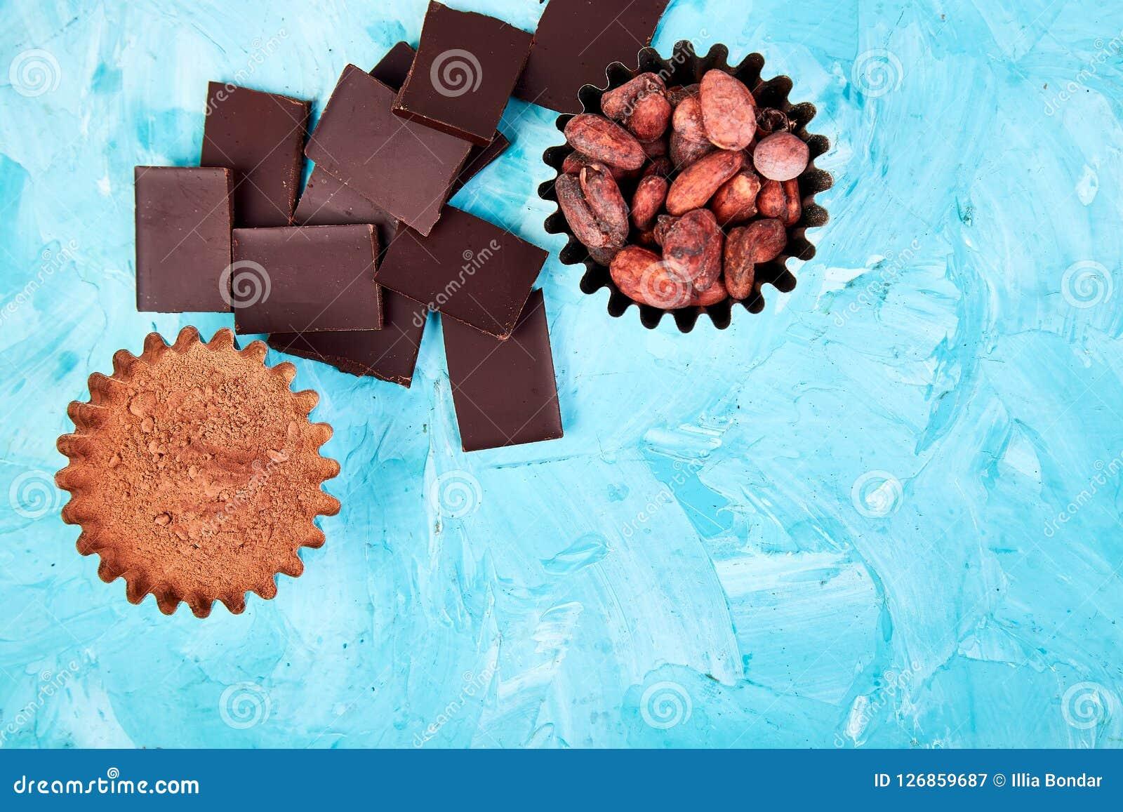 Bakgrund för kakaobönor på blåtttabellen Mörkerchoklad lappar