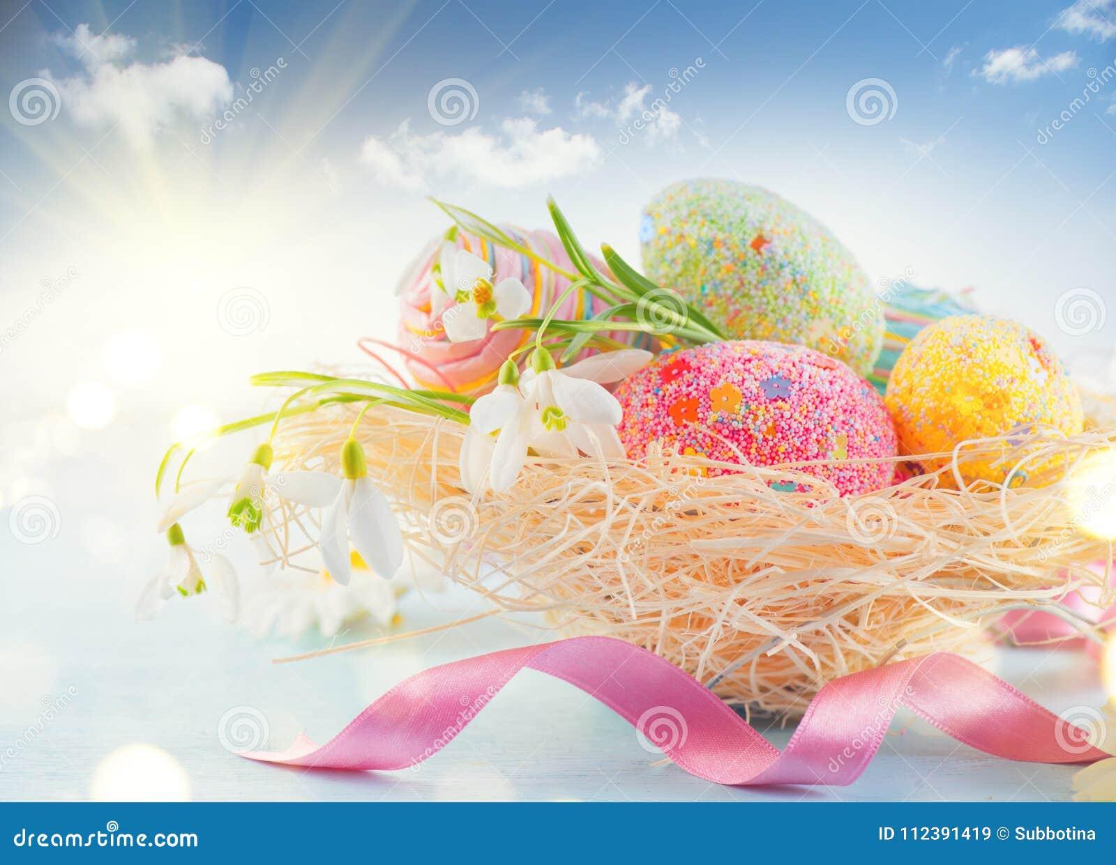 Bakgrund för påskferieplats Traditionella färgrika ägg och vårblommor i redet över blå himmel