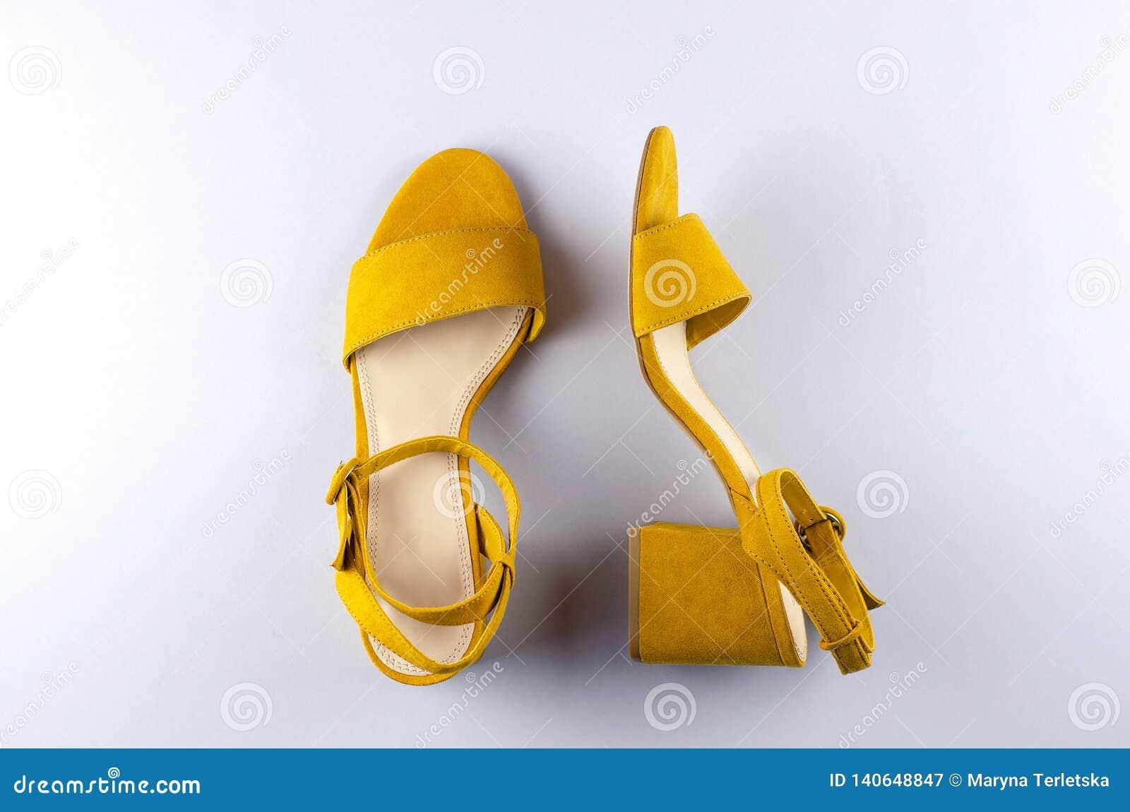 Bakgrund för senapsgult färg för två sandaler grå