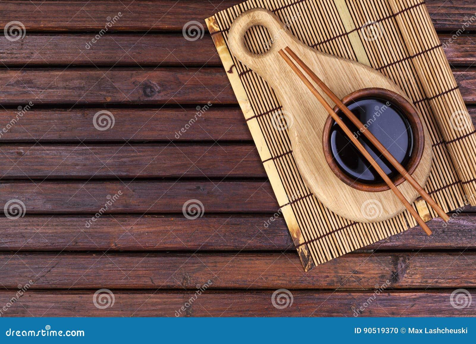 Bakgrund för sushi Matt bambu, soya, pinnar på trätabellen Utrymme för bästa sikt och kopierings