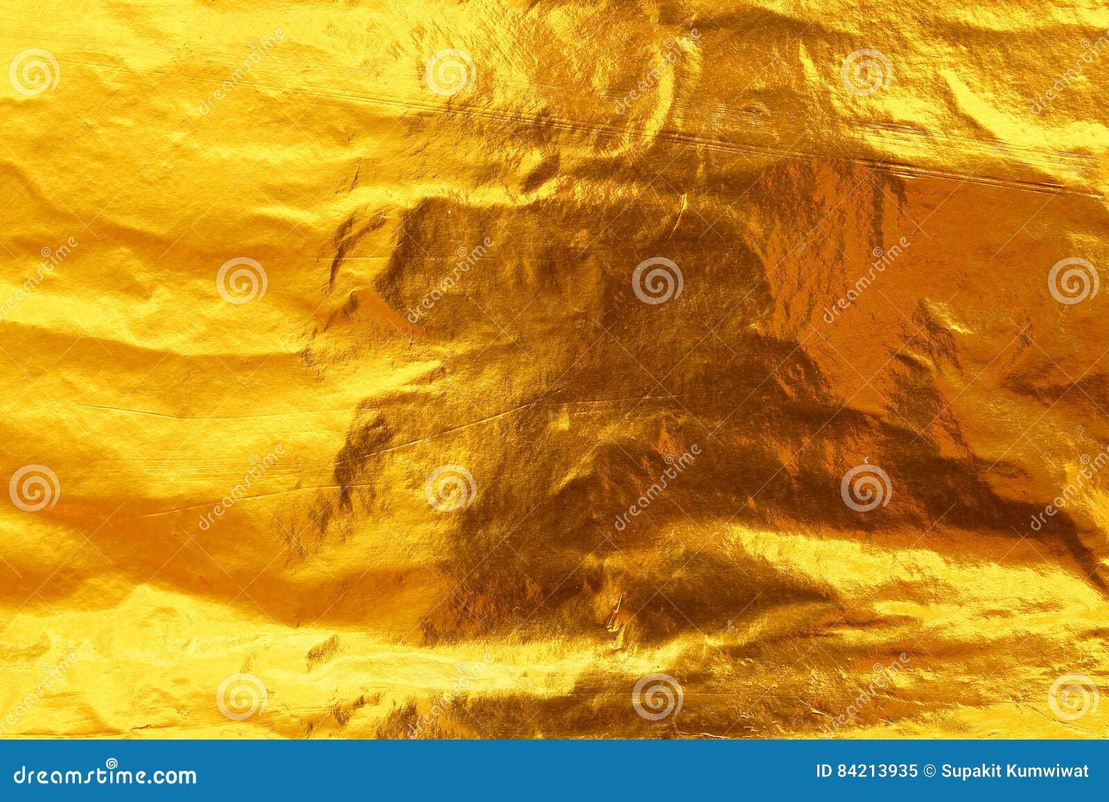 Bakgrund för textur för guld- folie för skinande gult blad mörk