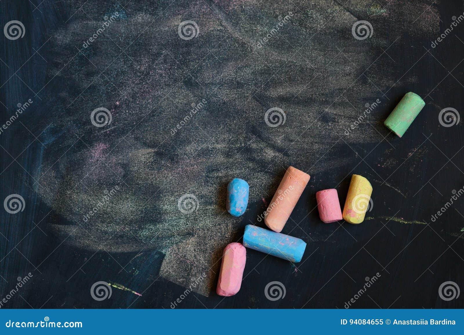 Bakgrund med den färgrika skolan chalks på en svart svart tavla