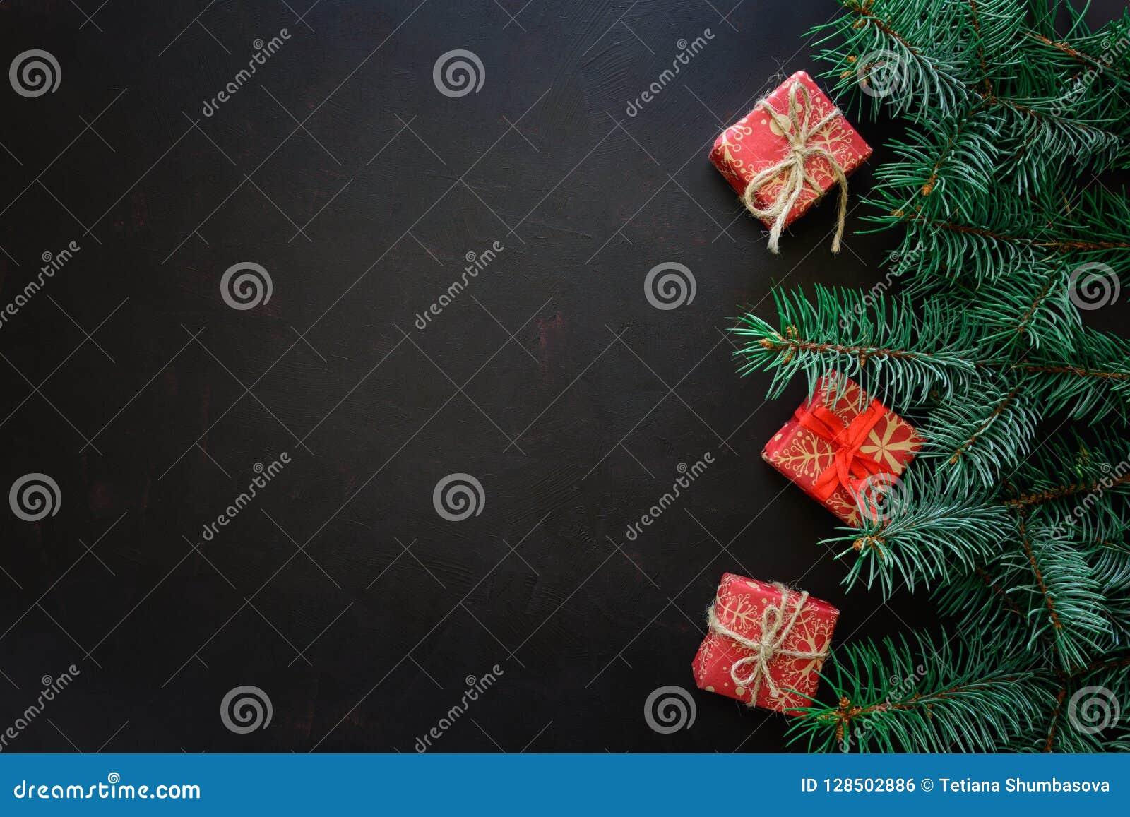 Bakgrundskanten boxes vita guld- isolerade band för julgåvan Granträdfilialer med gåvaaskar på mörk träbakgrund