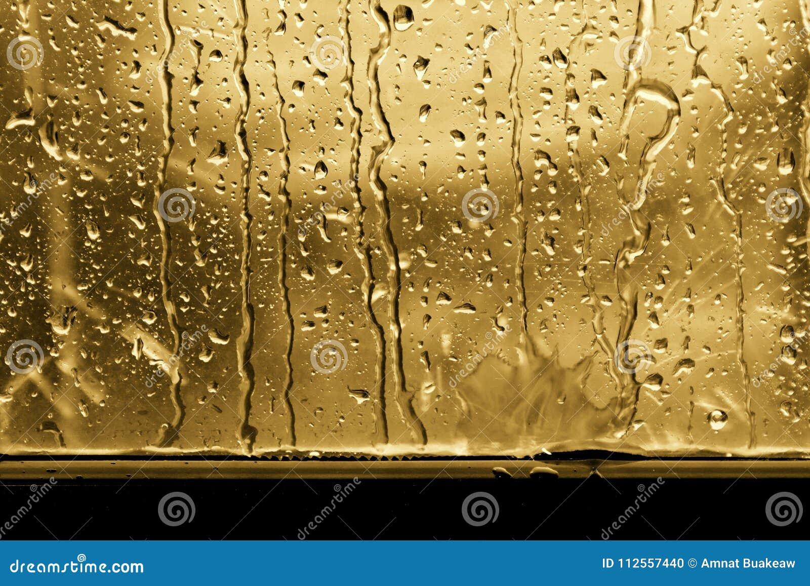 Bakgrundsregndroppe på guld eller guling för fönsterexponeringsglas