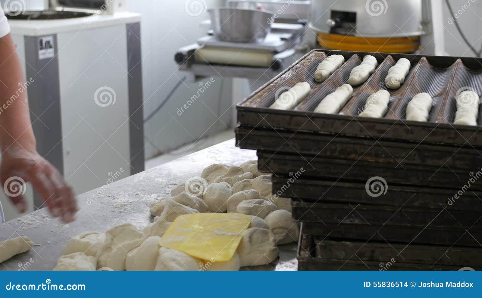 Bakkerijarbeider die zachte broodjes in industriële keuken maken