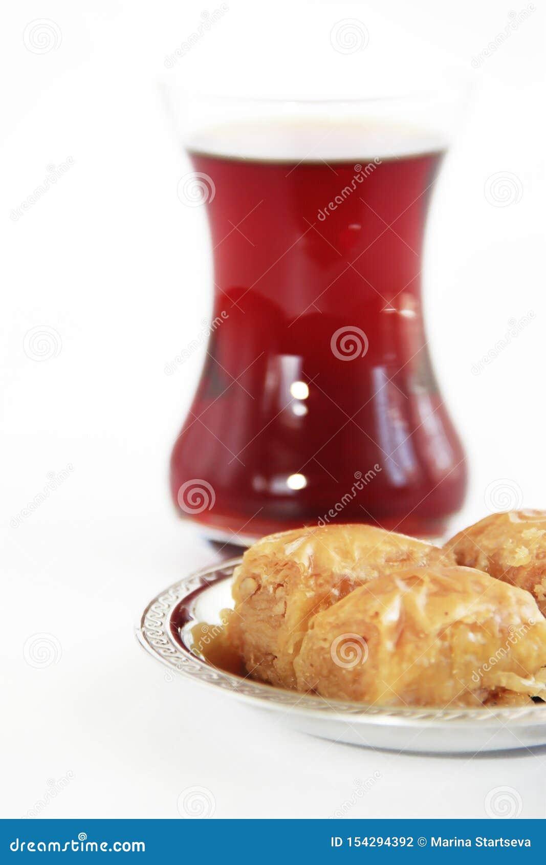 Baklava turca nazionale tradizionale di dolcezza sul piatto decorativo e su un vetro di tè
