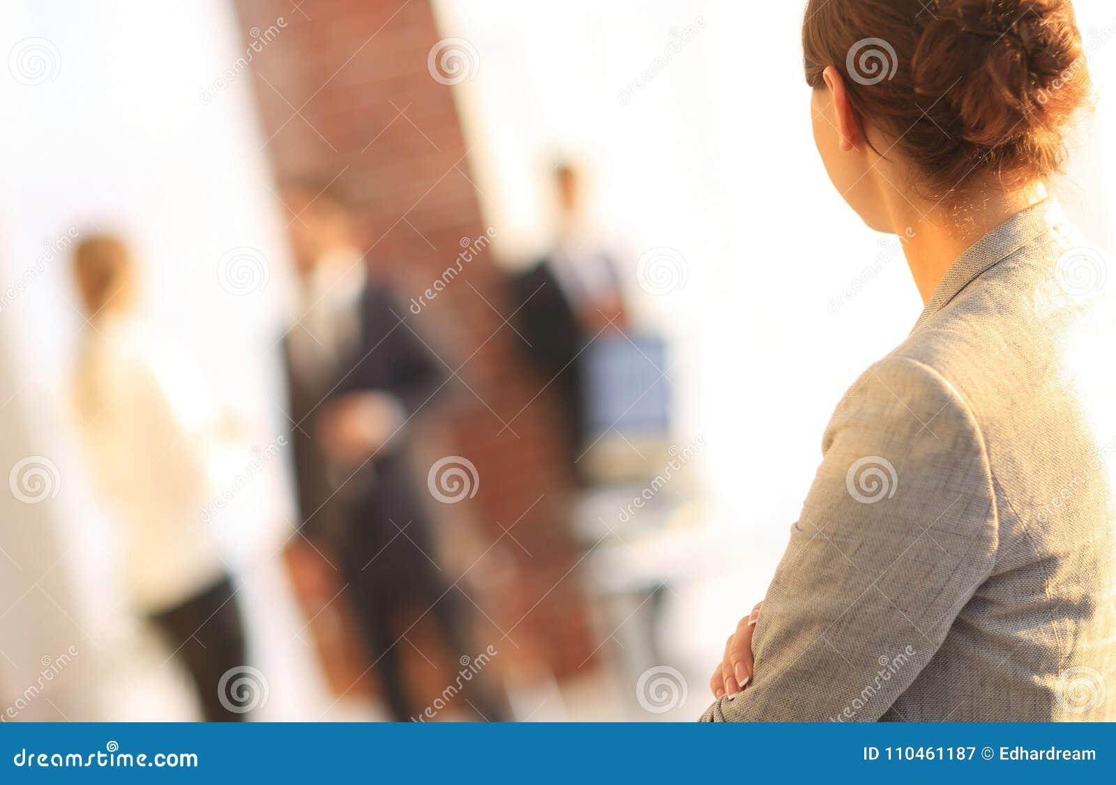 Bakre sikt av affärskvinnan på suddigt bakgrundskontor