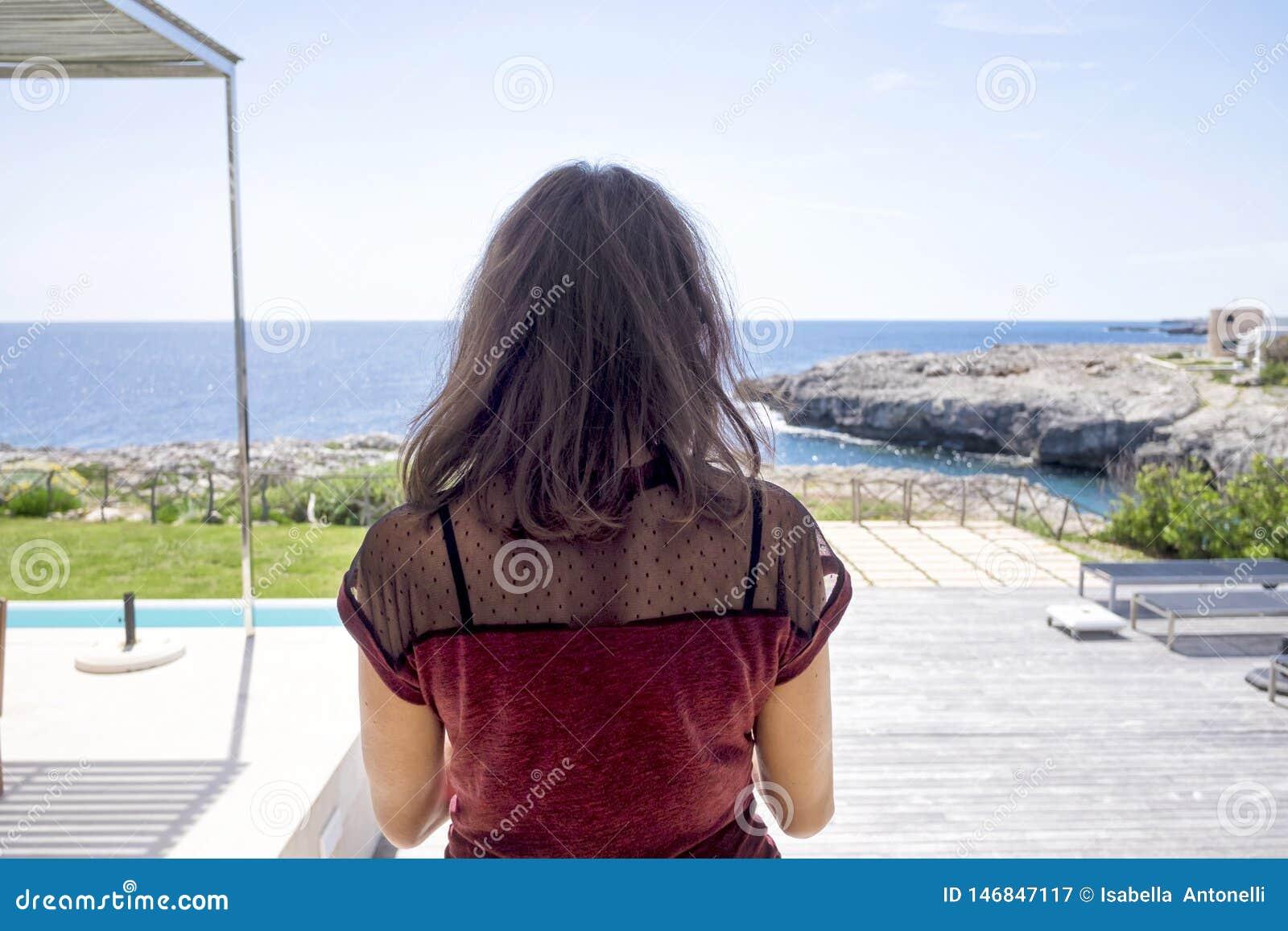 Bakre sikt av anseendet f?r ung kvinna p? terrassen som bort ser till havshorisonten i en solig dag