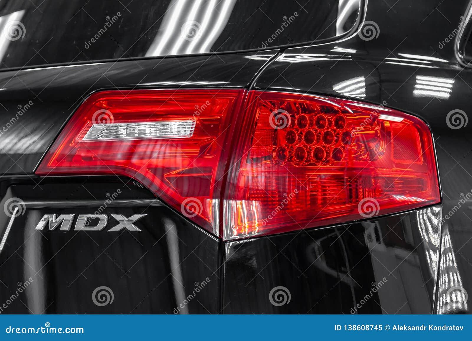 Bakre sikt av använda Acura MDX 2008 år svartfärg med röda taillamps som står i den ljusa serviceasken av det specificera seminar