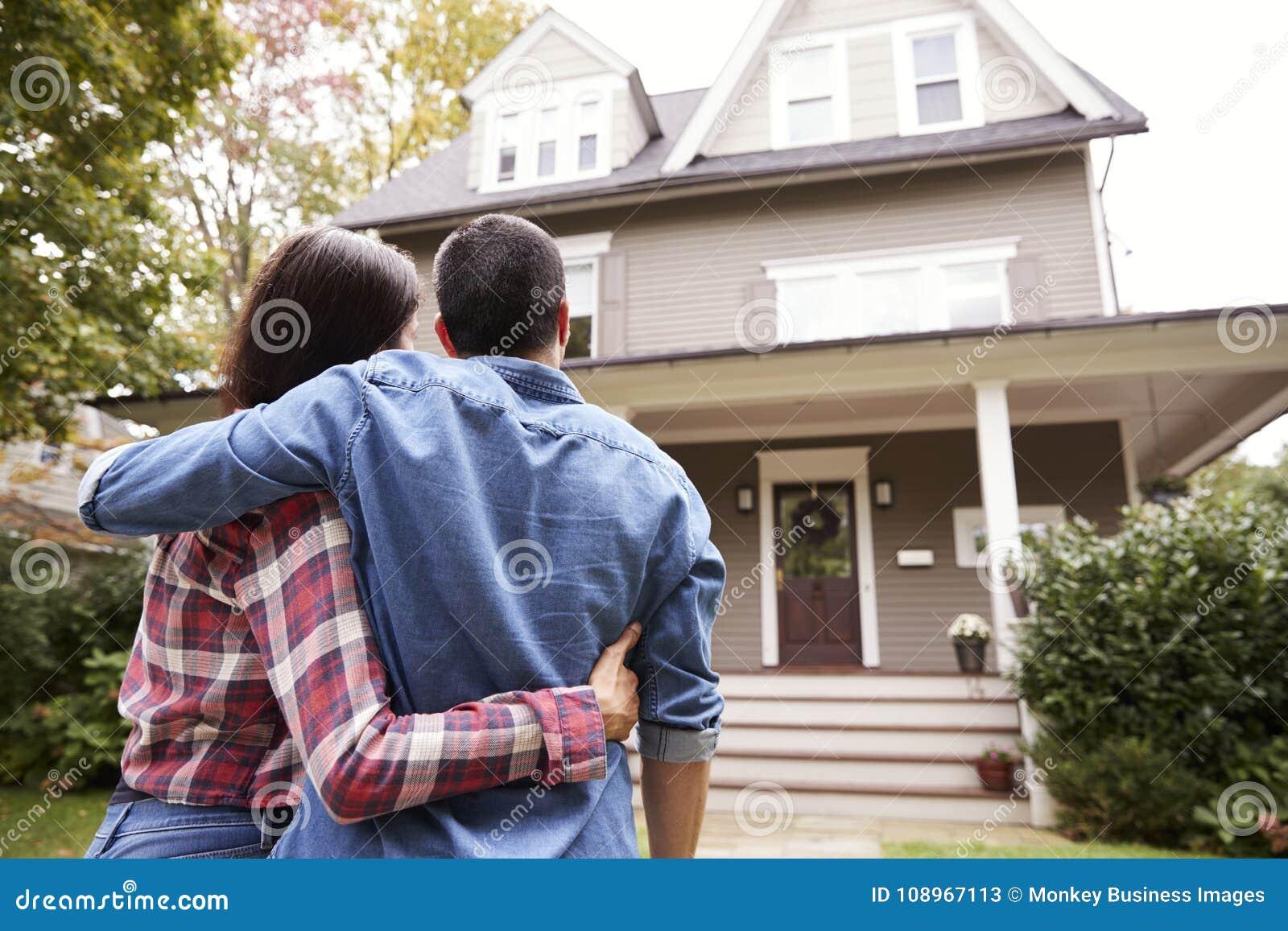 Bakre sikt av att älska par som ser huset