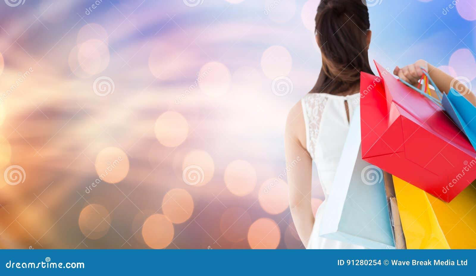 Bakre sikt av bärande shoppingpåsar för kvinnlig över bokeh