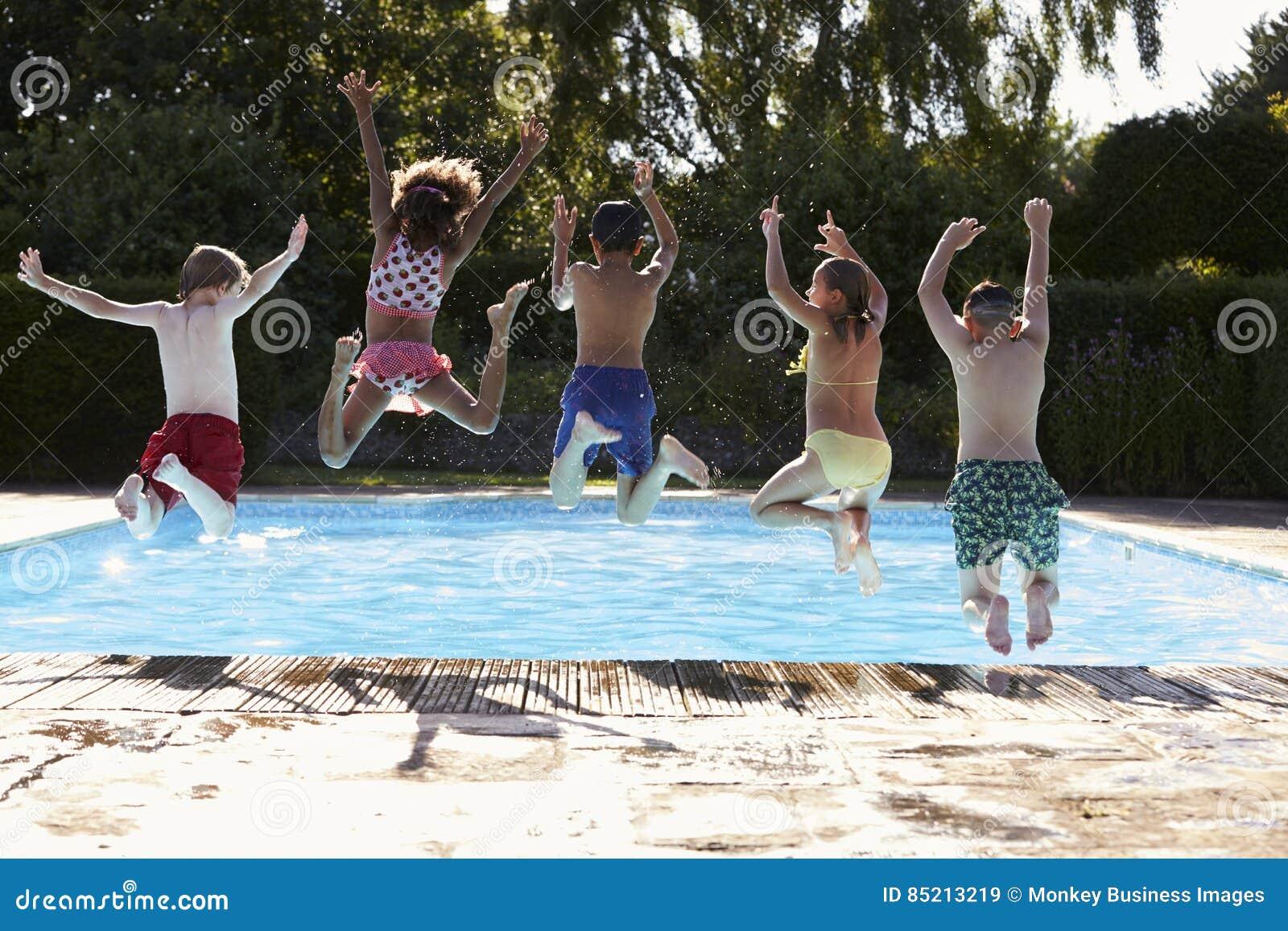 Bakre sikt av barn som hoppar in i utomhus- simbassäng