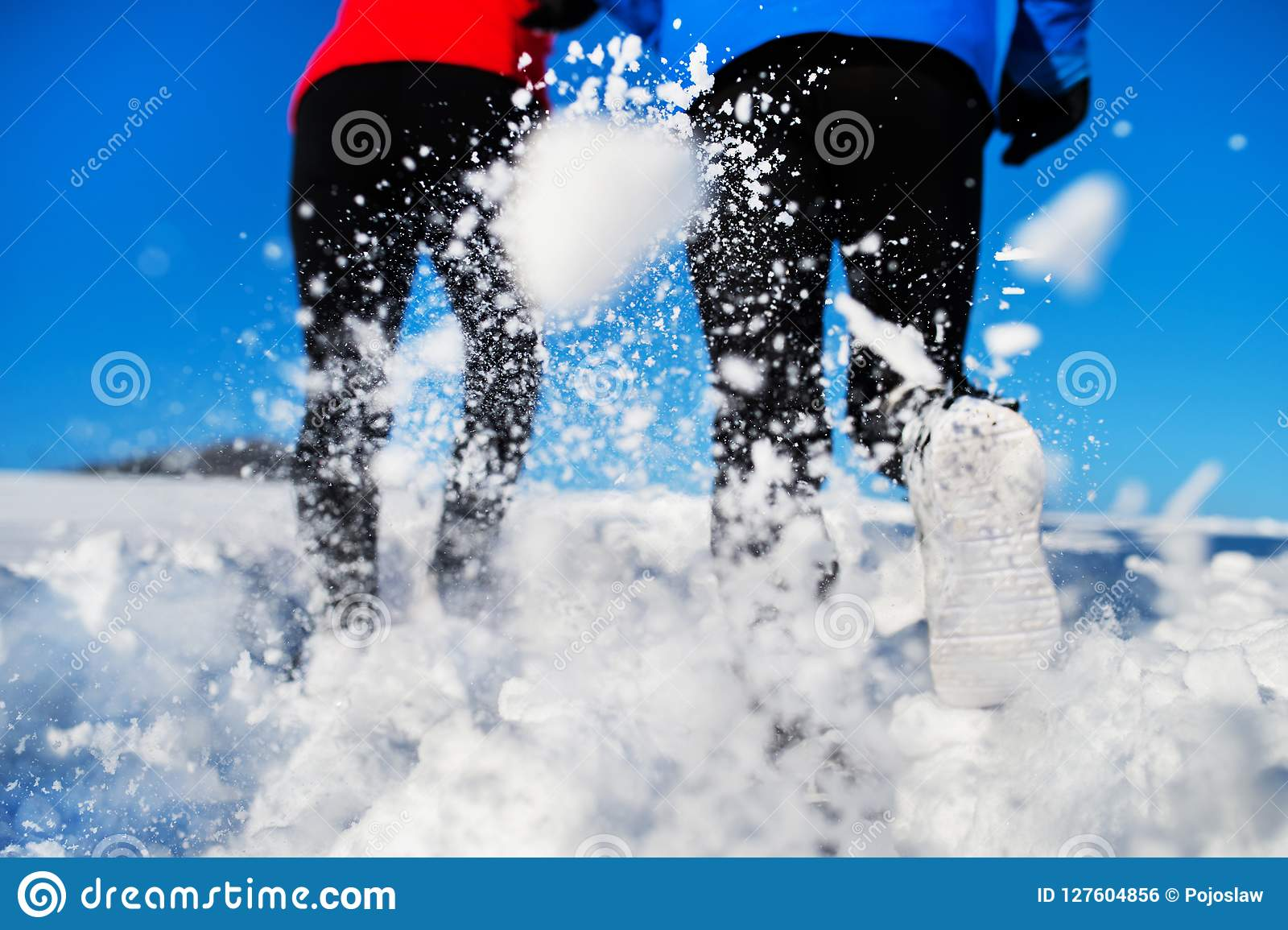 Bakre sikt av ben av höga par som joggar i vinternatur