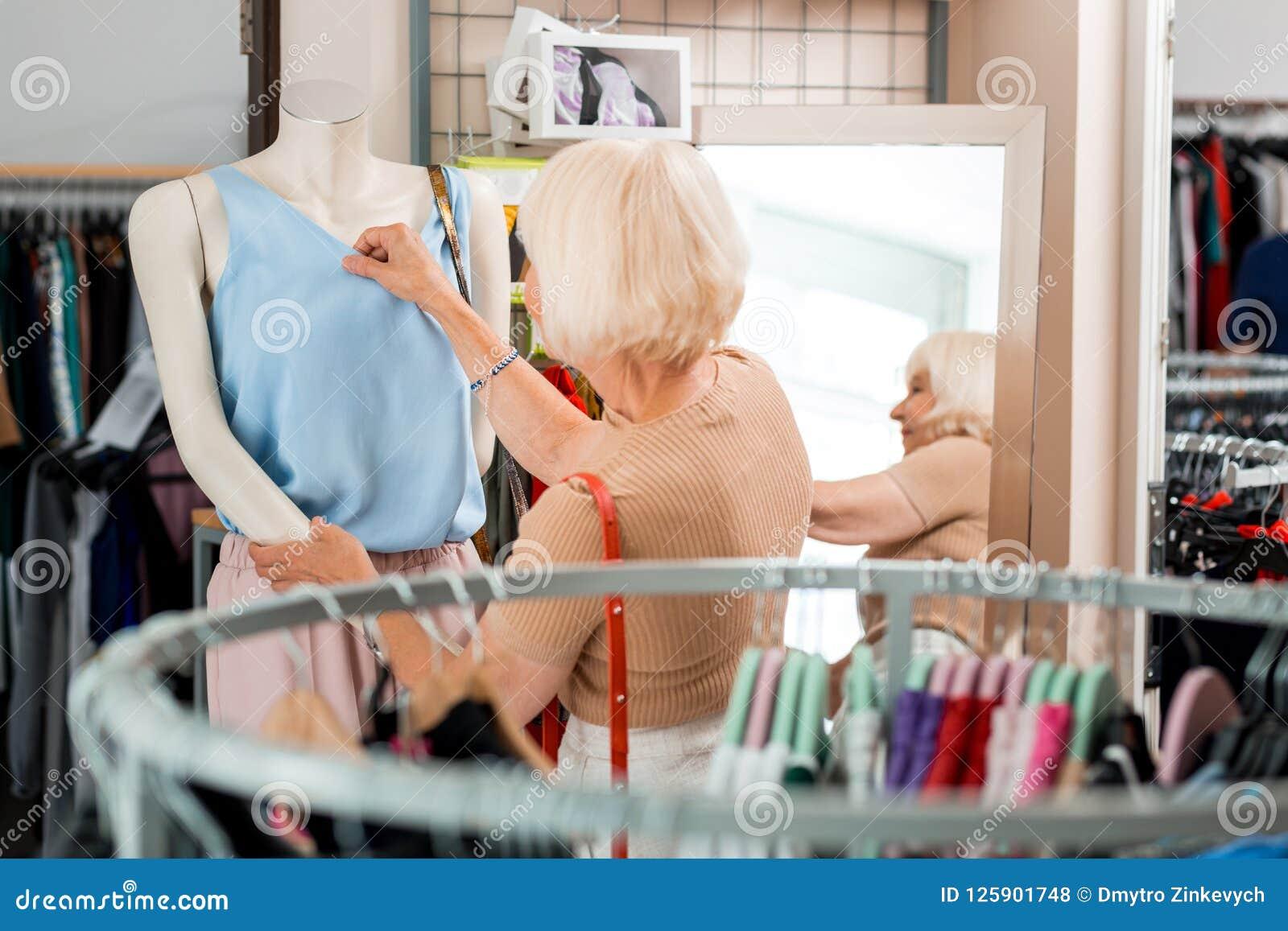 Bakre sikt av den äldre eleganta kvinnan som kontrollerar kläder som är kvalitets- på shoppinglagret