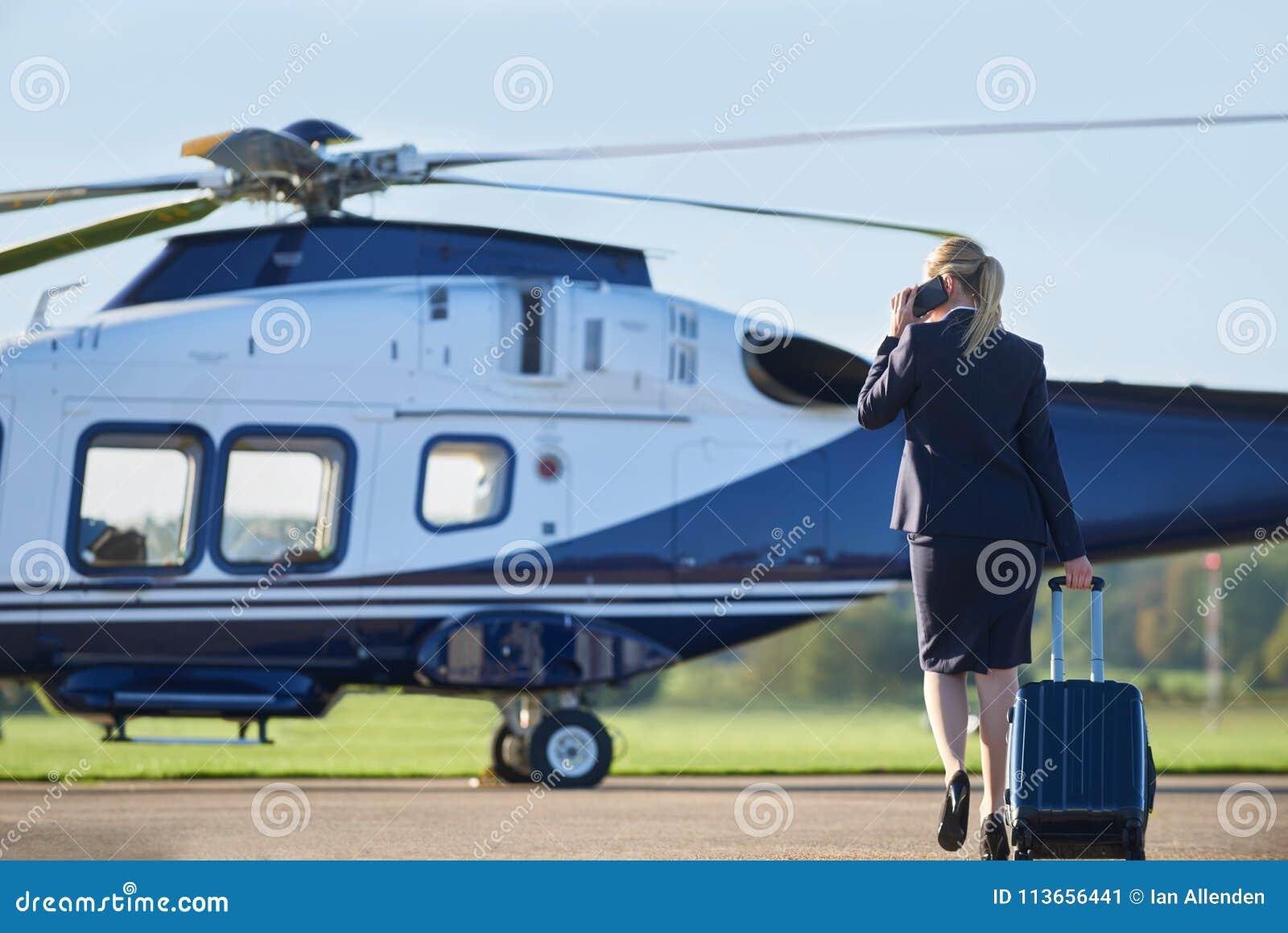 Bakre sikt av den affärskvinnaWalking Towards Helicopter stunden Tal