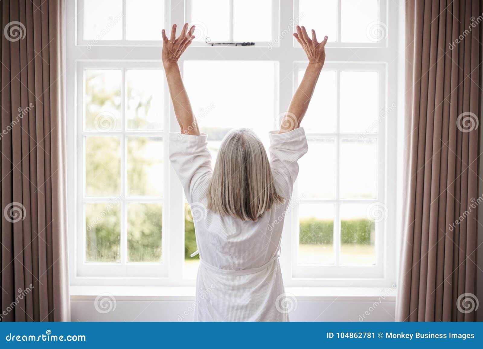 Bakre sikt av den höga kvinnan som sträcker i Front Of Bedroom Window