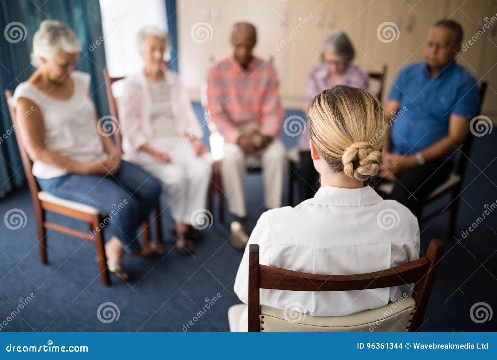 Bakre sikt av den kvinnliga doktorn som mediterar med högt folk