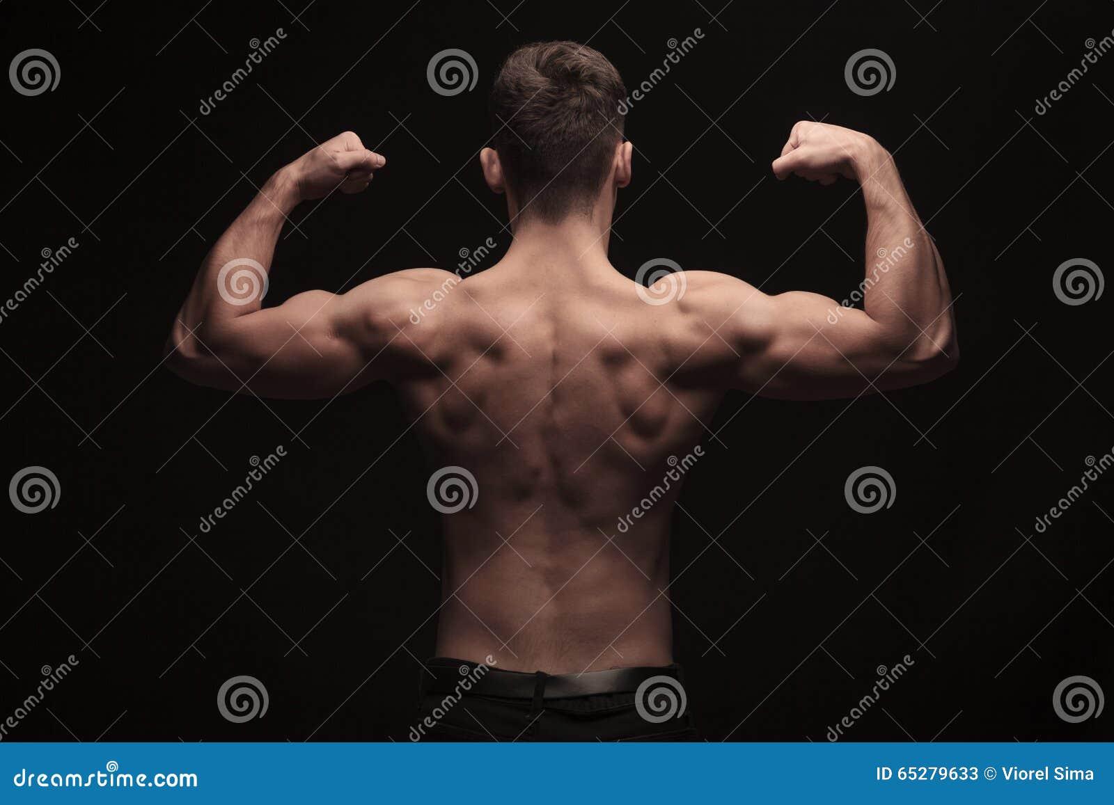 Bakre sikt av den topless muskulösa mannen som poserar i studio