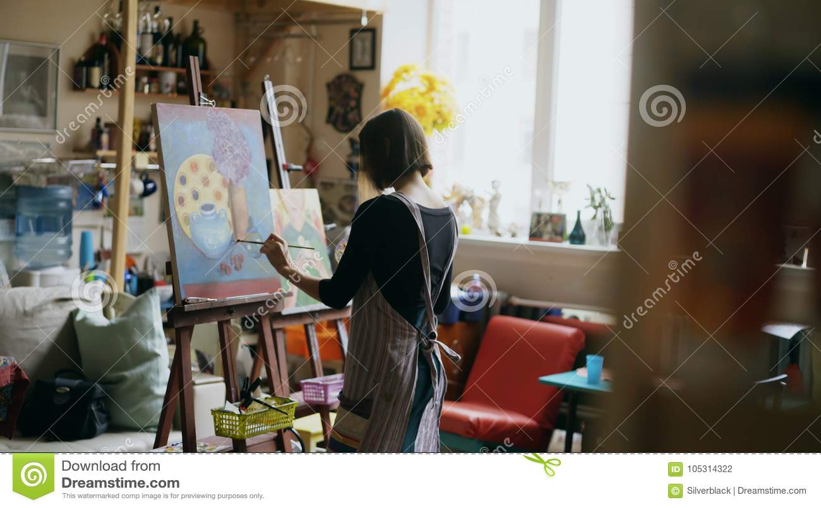 Bakre sikt av den unga målareflickan i bild för förklädemålningstilleben på kanfas i konst-grupp