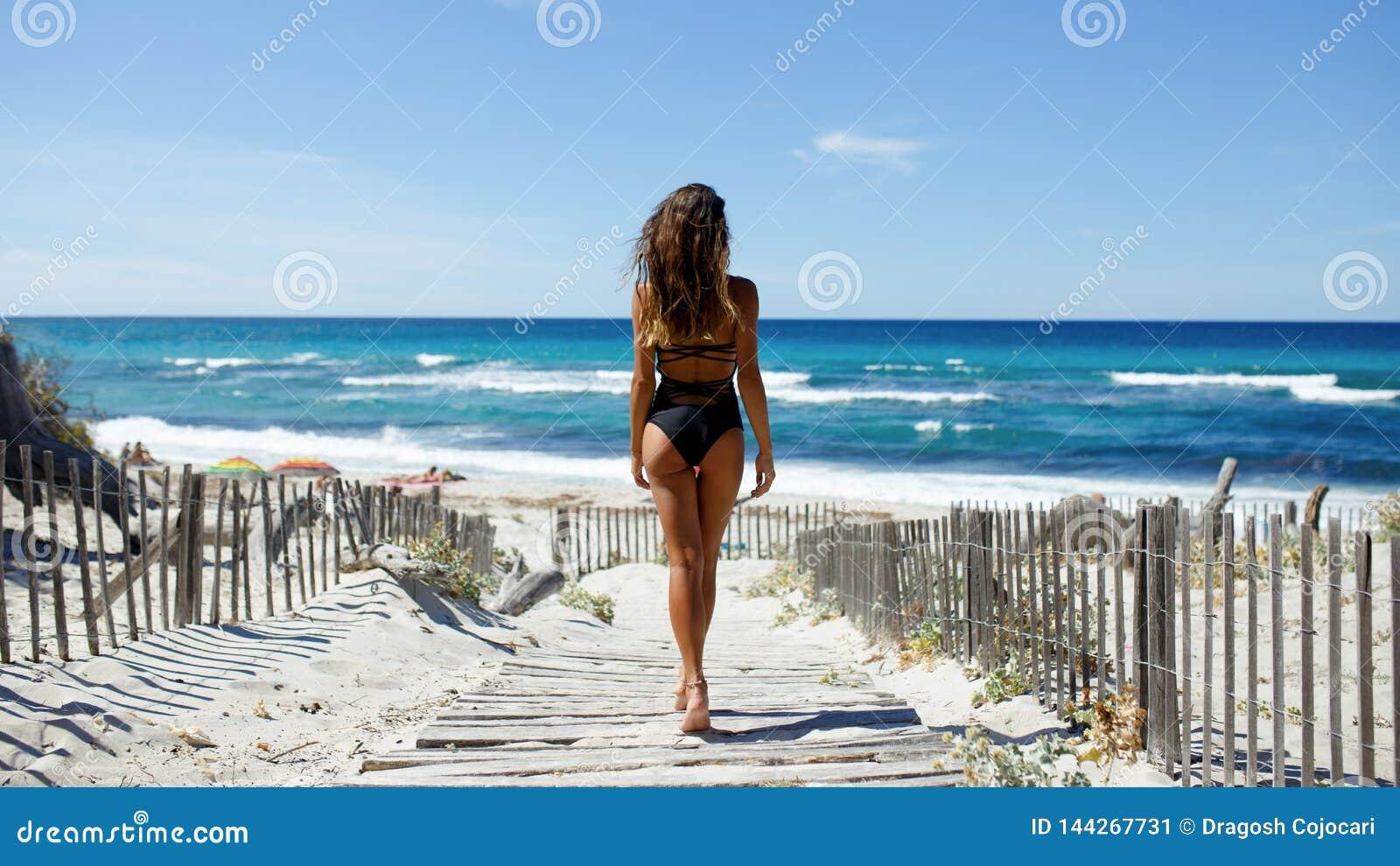Bakre sikt av en härlig ung kvinna som poserar på stranden Hav strand, sand, himmelbakgrund