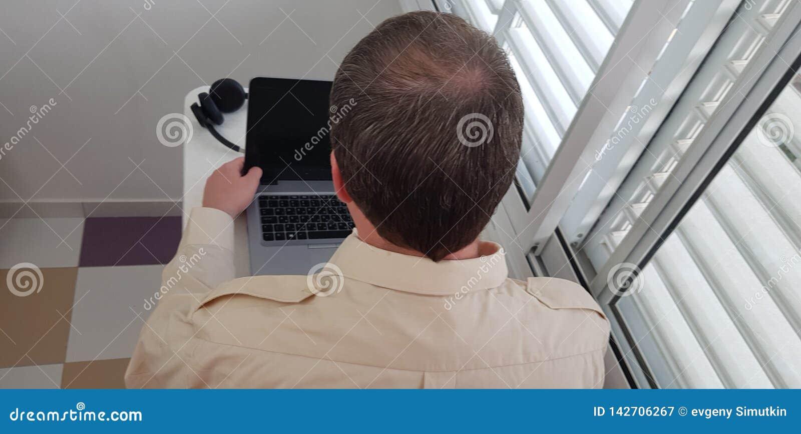 Bakre sikt av en man som bär den officiella krageskjortan som sitter nära fönster