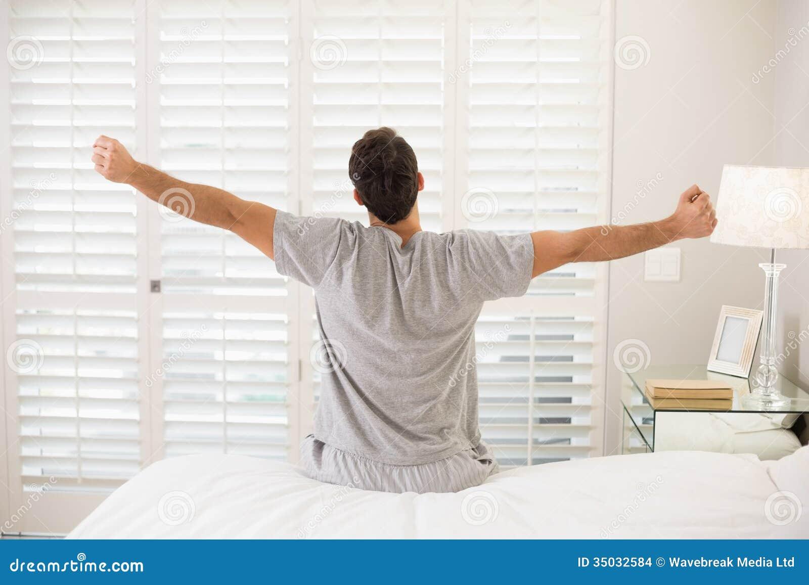 Bakre sikt av en man som sträcker hans armar i säng