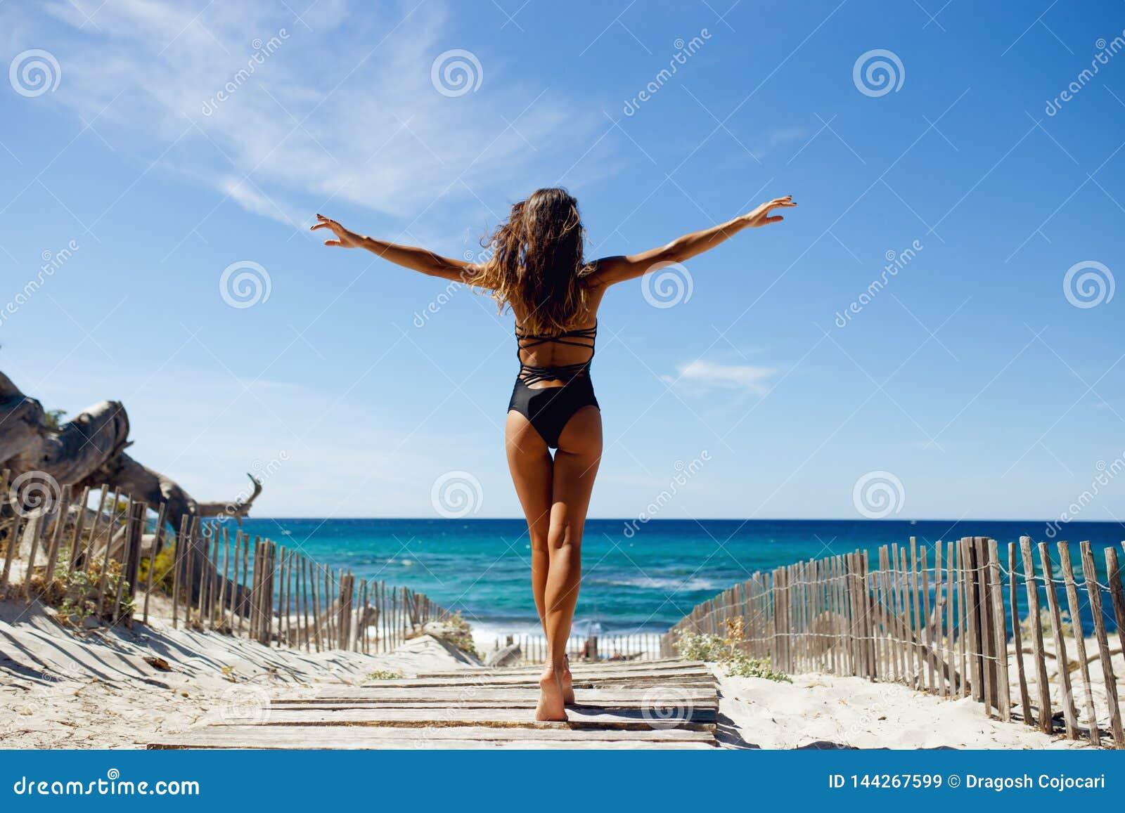 Bakre sikt av ett härligt, brunettung flicka med lyftta händer som ser havet