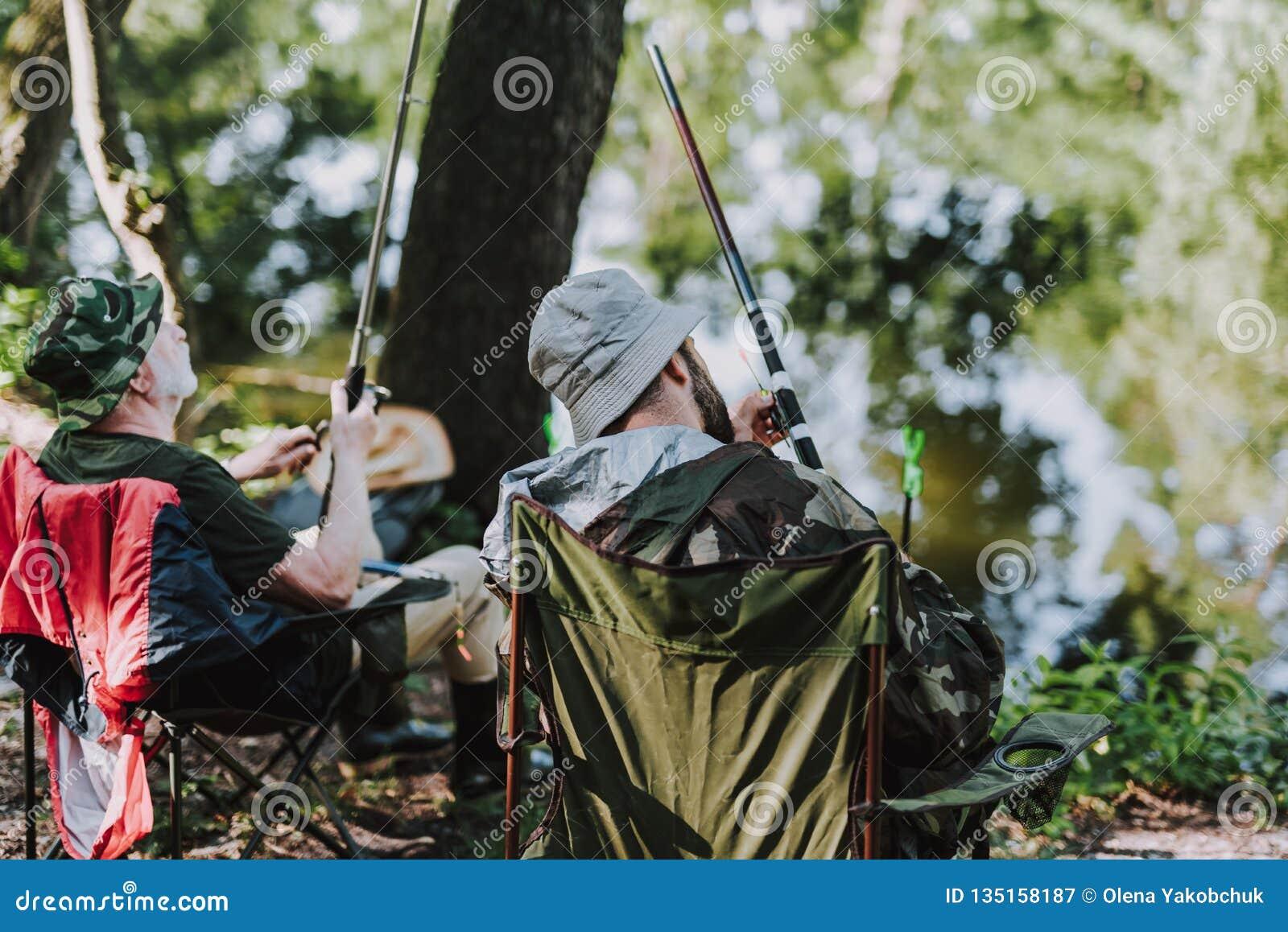 Bakre sikt av förtjusta män som tycker om att fiska på flodbanken