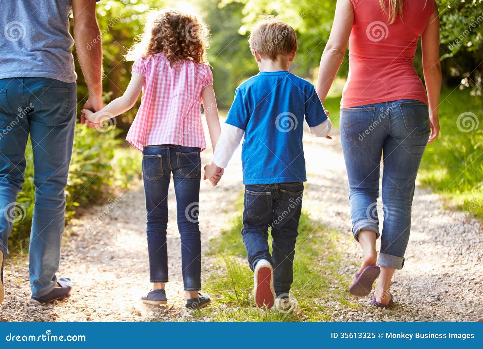 Bakre sikt av familjen som går i bygd