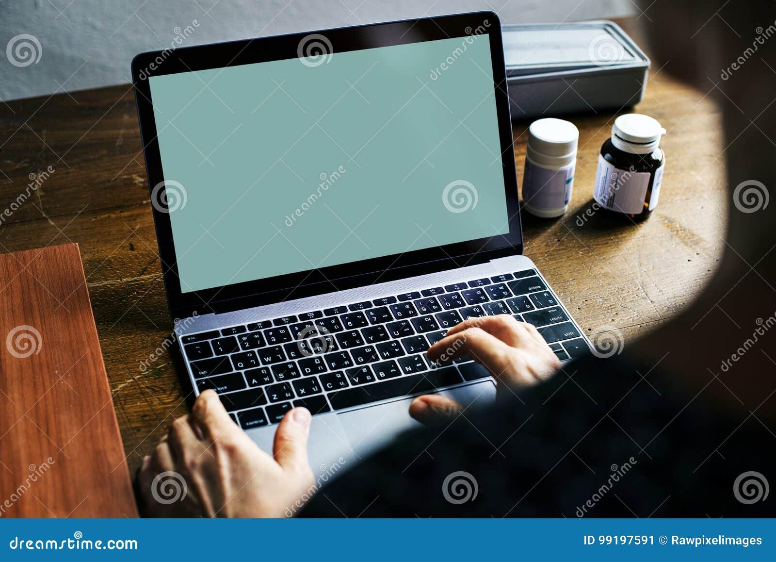 Bakre sikt av folk som använder datorbärbara datorn som visar den tomma gröna skärmen