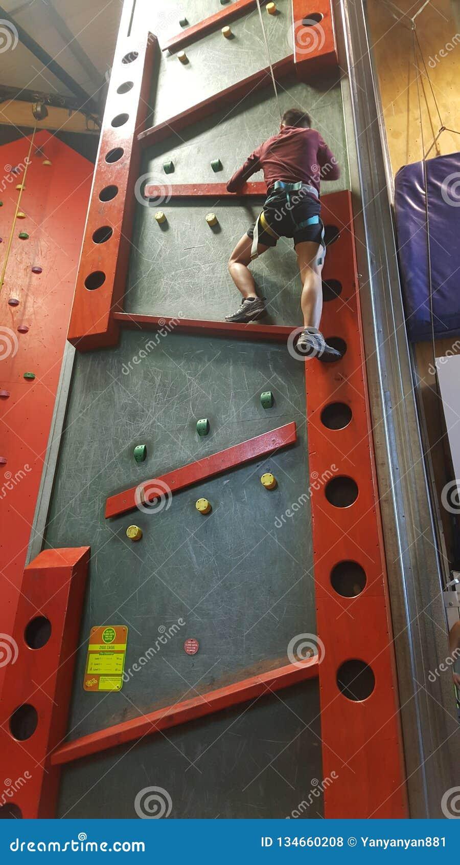 Bakre sikt av klättraren som inomhus flyttar sig upp för att vagga att klättra