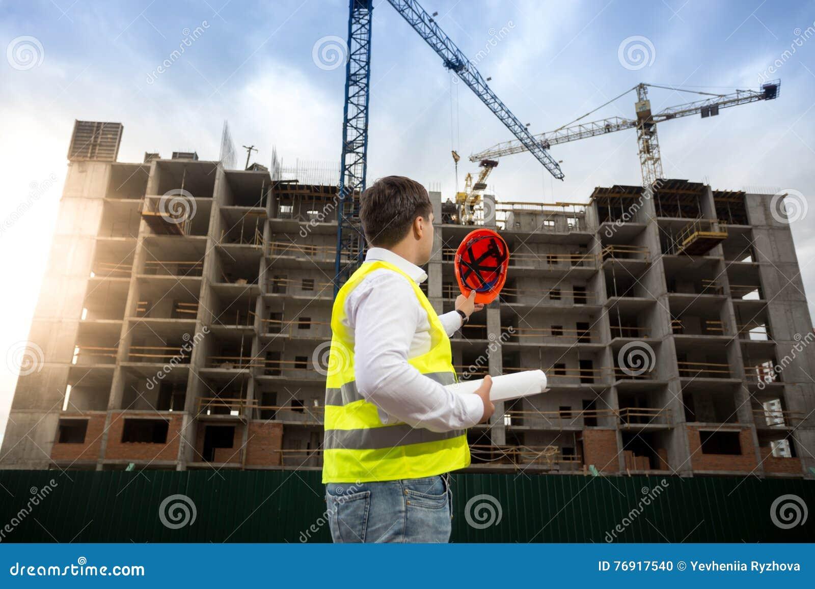 Bakre sikt av konstruktionsteknikern som poserar på byggnadsplats på su